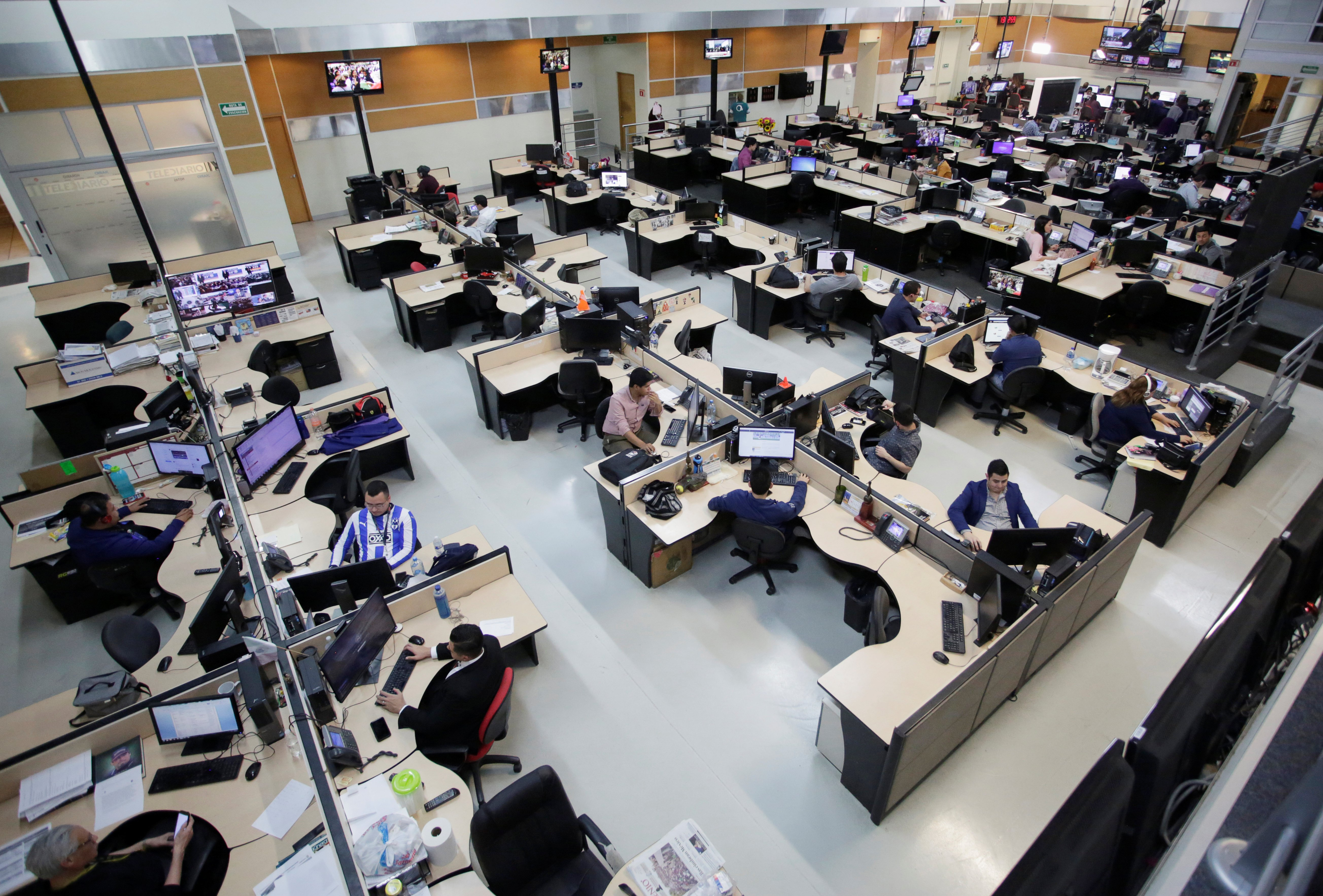 People work at the newsroom of Multimedios Television with empty desks of their female counterparts during