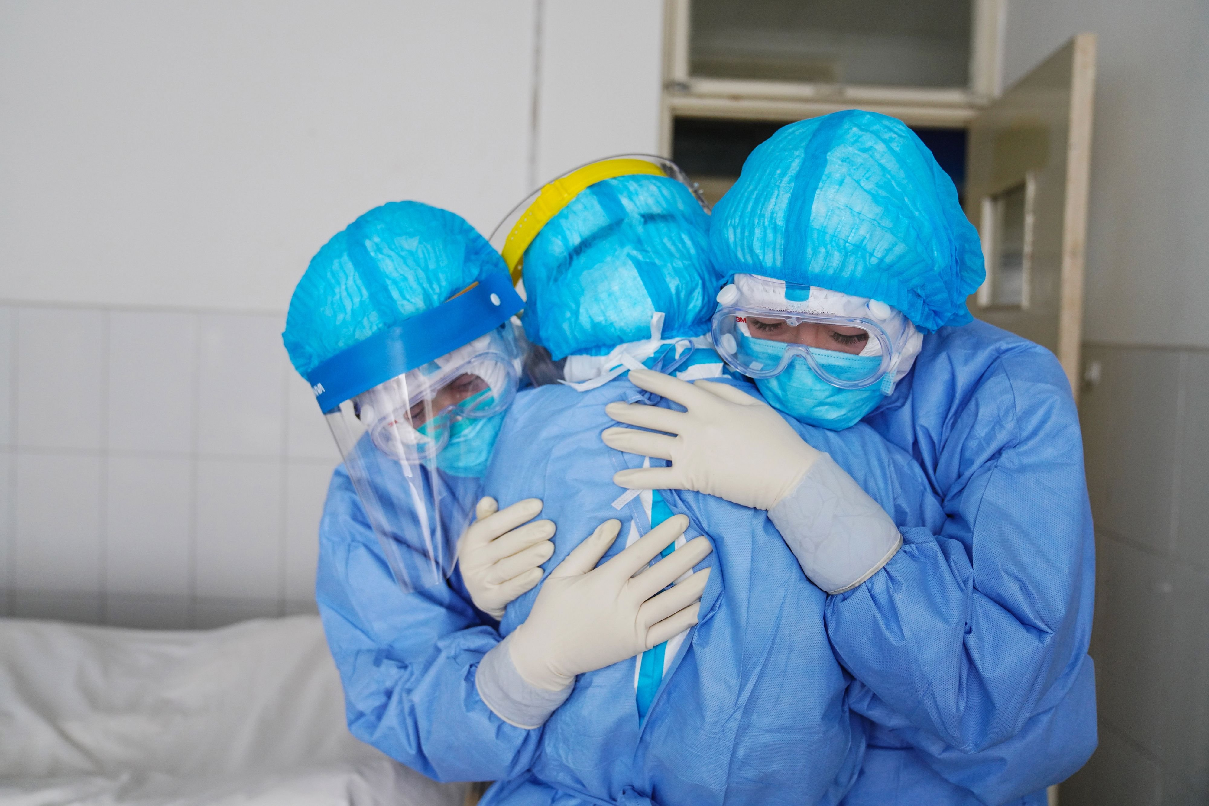 This file photo taken on January 28, 2020 shows medical staff members hugging each other in an isolation ward at a hospital in Zouping in China's easter Shandong province. (AFP Photo)