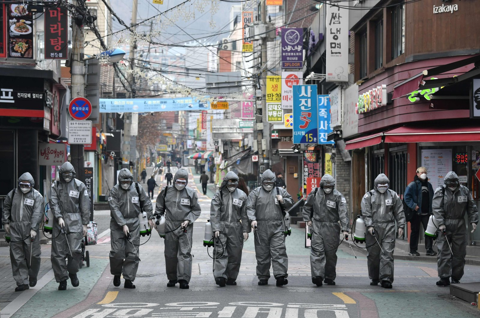 South Korean soldiers wearing protective gear spray disinfectant to help prevent the spread of the COVID-19 coronavirus, at a shopping district in Seoul, March 4, 2020. (AFP Photo)