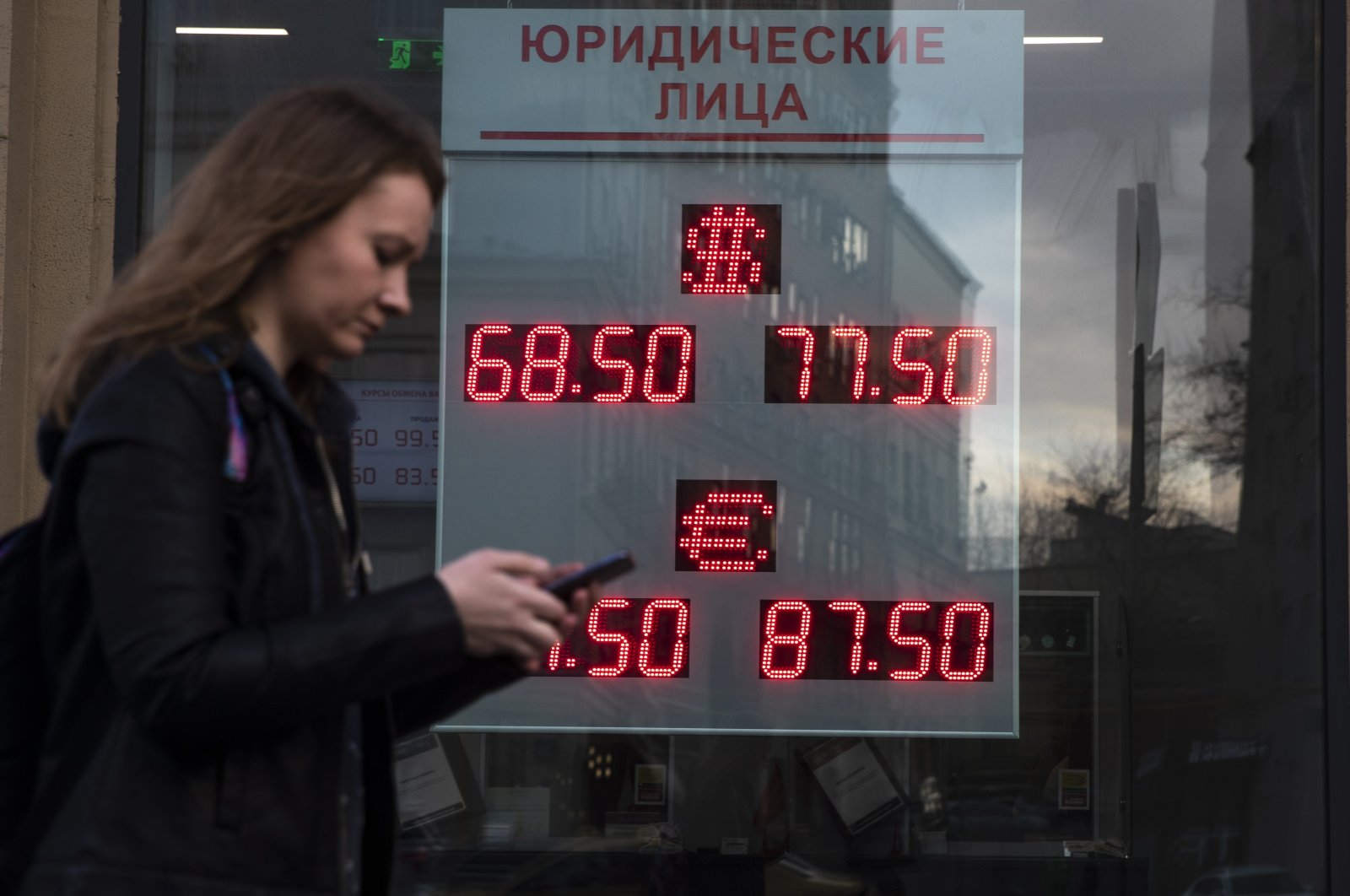 A woman walks past an currency exchange office screen displaying the exchange rates of U.S. Dollar and Euro to Russian Rubles, in Moscow, Russia, Monday, March 9, 2020. (AP Photo)