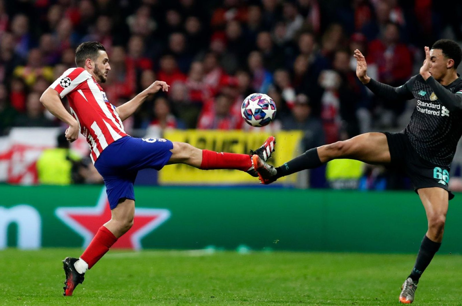 Atletico Madrid's Koke and Liverpool's Alexander-Arnold fight for the ball during a Champions League match in Madrid, Feb. 18, 2020. (AP Photo)