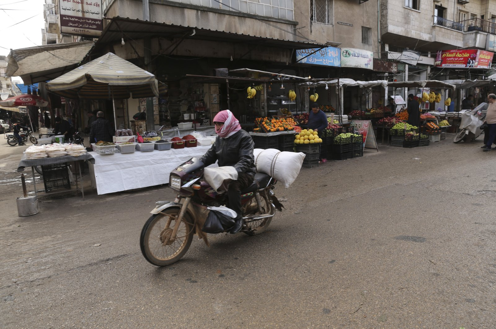Man rides a motorcycle through a market in the city of Idlib during the ceasefire, March 9, 2020. (AP Photo)