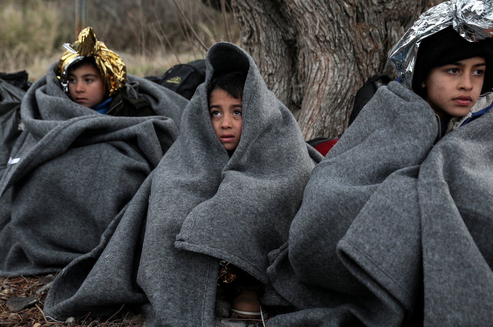 Children are covered with blankets and thermal blankets after migrants from Afghanistan arrived on a dinghy on a beach near the village of Skala Sikamias on the island of Lesbos, Feb. 28, 2020. REUTERS