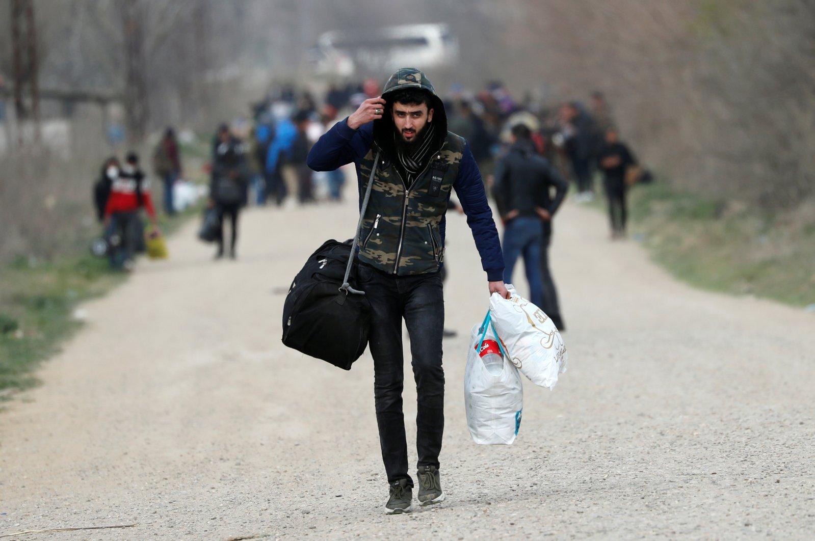 A migrant walks near Turkey's Pazarkule border crossing with Greece's Kastanies, in Edirne, March 10, 2020. REUTERS