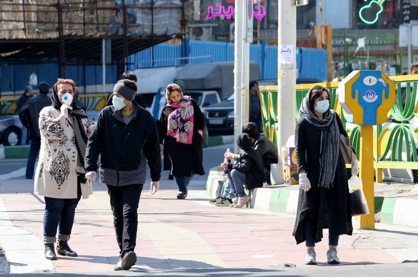Iranian pedestrians walk while wearing protective masks in Tehran on March 10, 2020 amid the spread of coronavirus in the country. (AFP Photo)