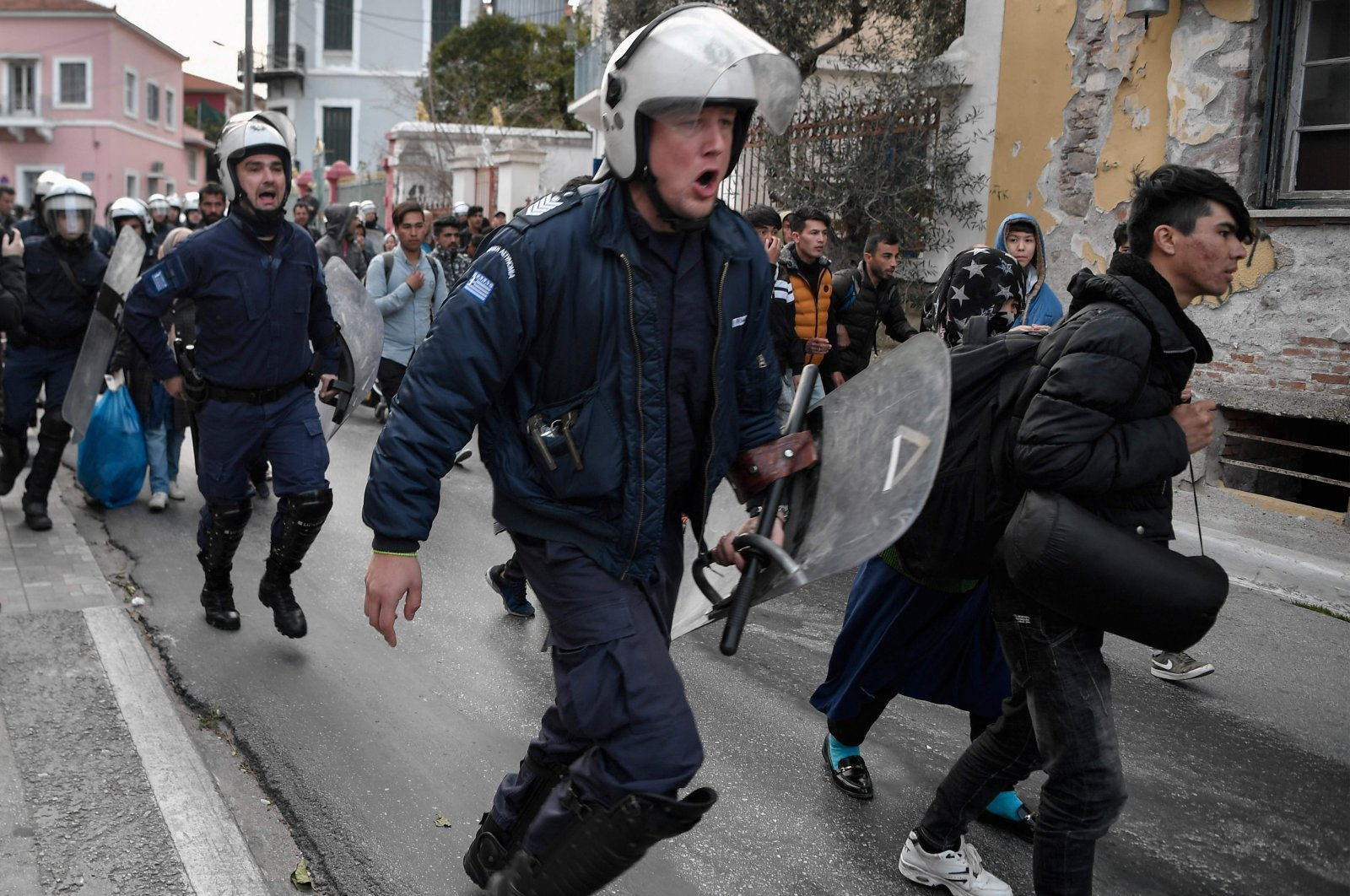 Greek anti-riot police run after migrants and refugees from the Moria camp who gathered outside the port of Mytilene on the island of Lesbos, hoping to get a ferry to Athens, on March 4, 2020. (AFP Photo)