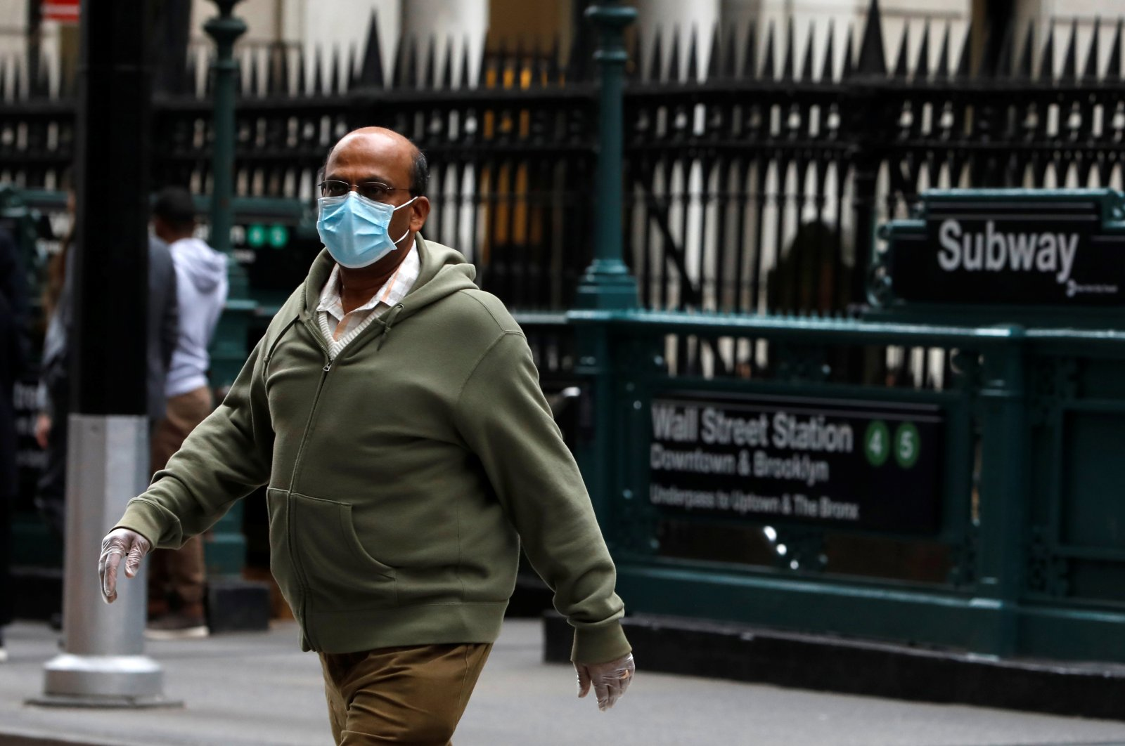 A man in a surgical mask and rubber gloves crosses Broadway in front of the Wall Street subway station after more cases of coronavirus were confirmed in New York, March 10, 2020. (Reuters Photo)