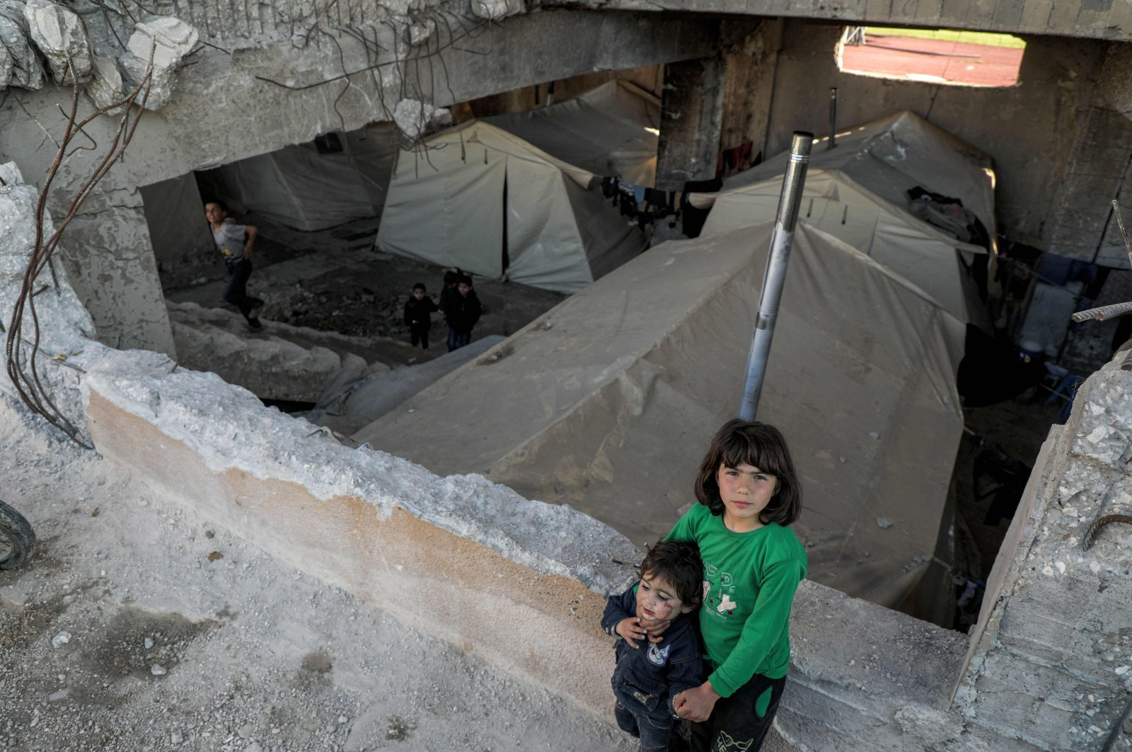 Syrian children displaced by the war stand in a makeshift camp at an Idlib football stadium on March 3, 2020, in the city of Idlib in northwestern Syria. (AFP Photo)
