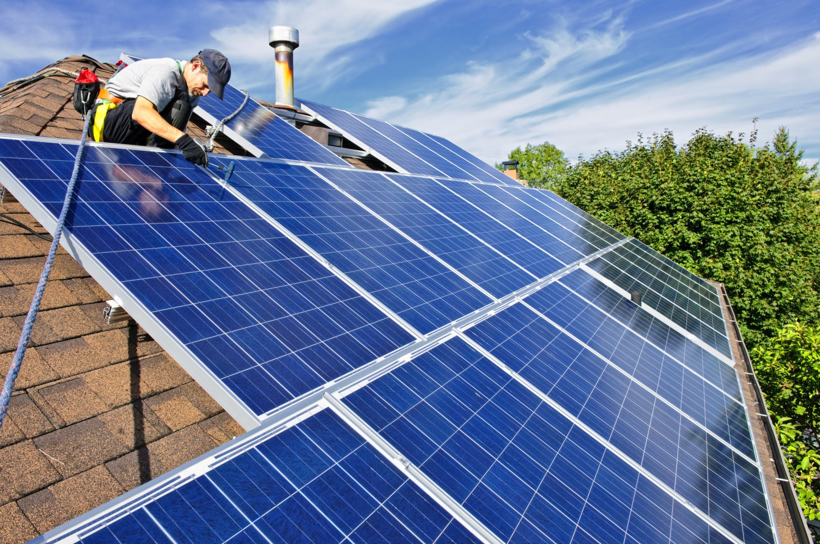 A man installs alternative energy photovoltaic solar panels on the roof. (iStock Photo)
