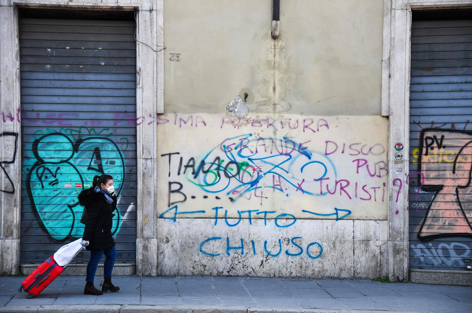 """A commuter wearing a protective mask walks past closed shops and an inscription on the wall reading """"All Closed,"""" Rome, March 11, 2020. (AFP Photo)"""