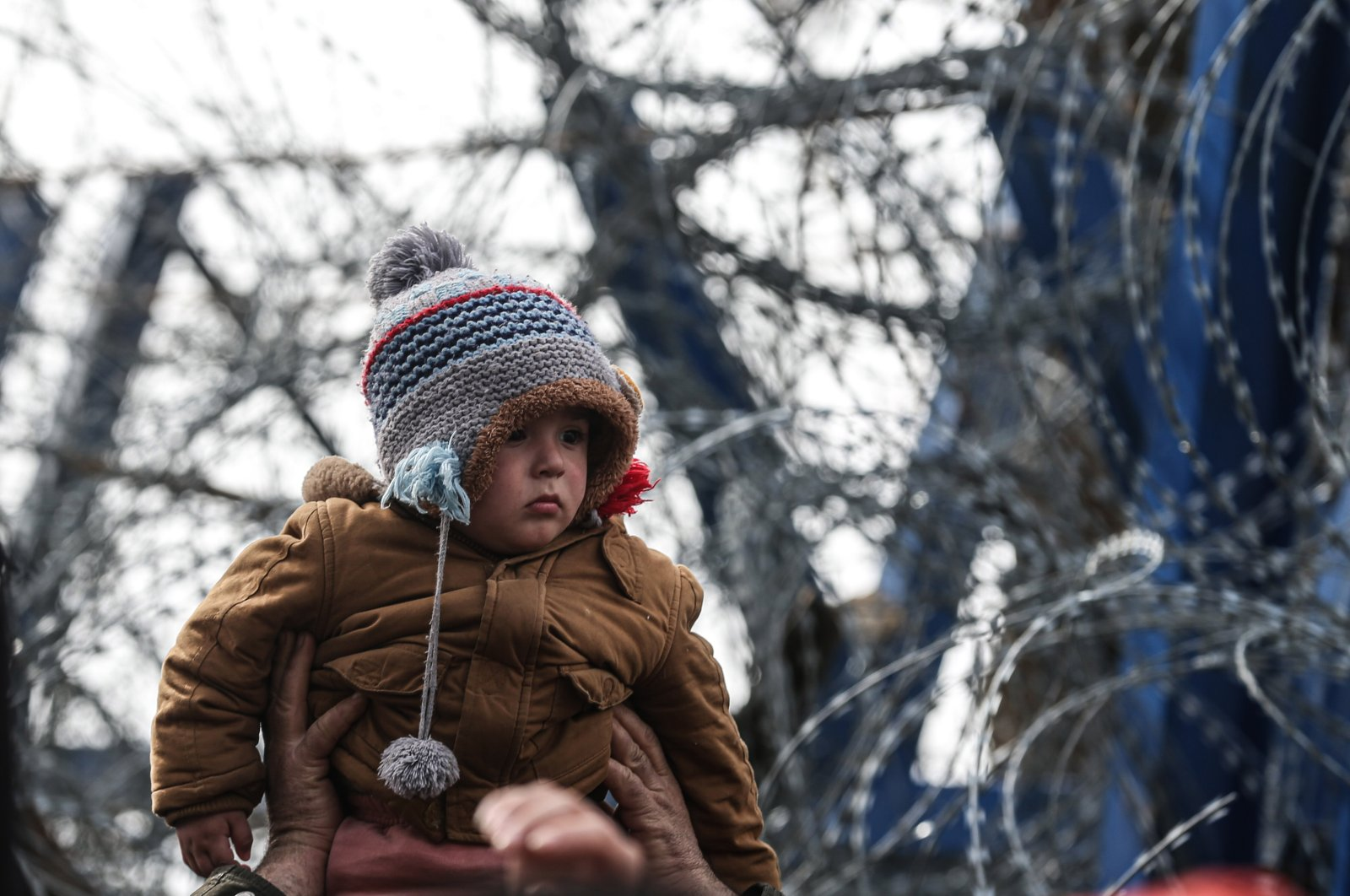 A child is seen waiting in front of wire ropes at the Turkish-Greek border. On the 13th day since asylum-seekers, refugees and other migrants started to gather at the Turkish-Greek border, the desperate wait for Europe to open its borders continues, March 8, 2020 (AA Photo)