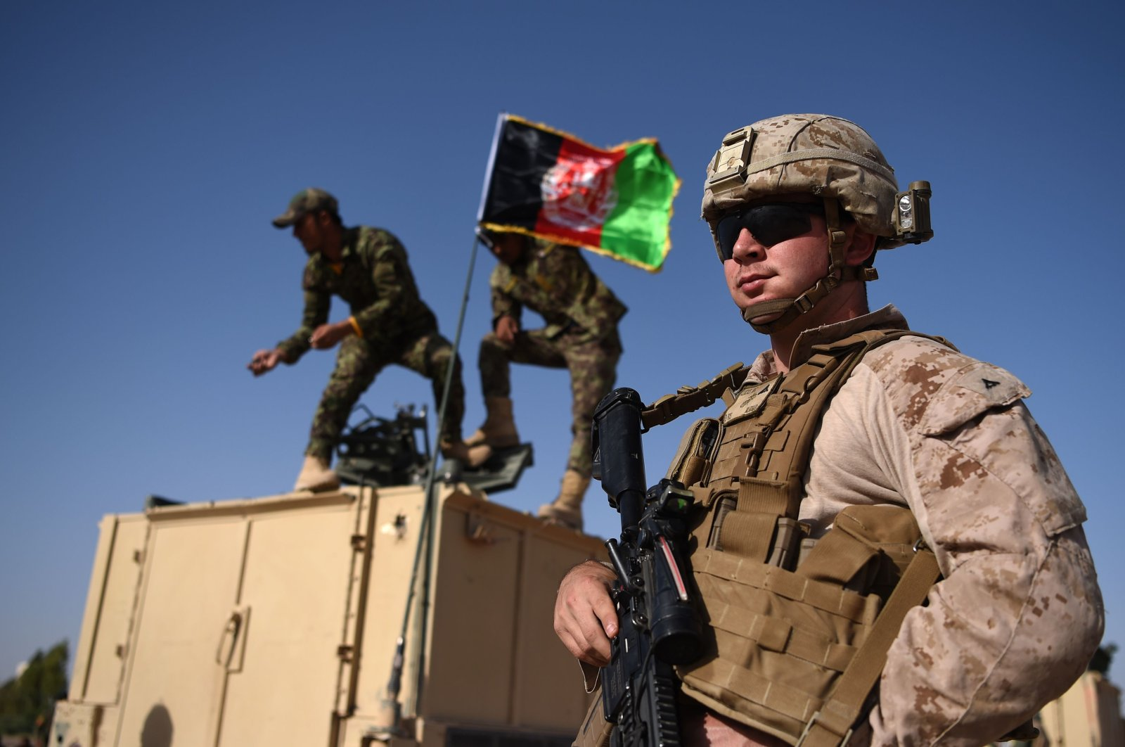 A US Marine looks on as Afghan National Army soldiers raise the Afghan National flag on an armed vehicle during a training exercise to deal with IEDs (improvised explosive devices) at the Shorab Military Camp in Lashkar Gah in Helmand province, Aug. 28, 2017. (AFP)