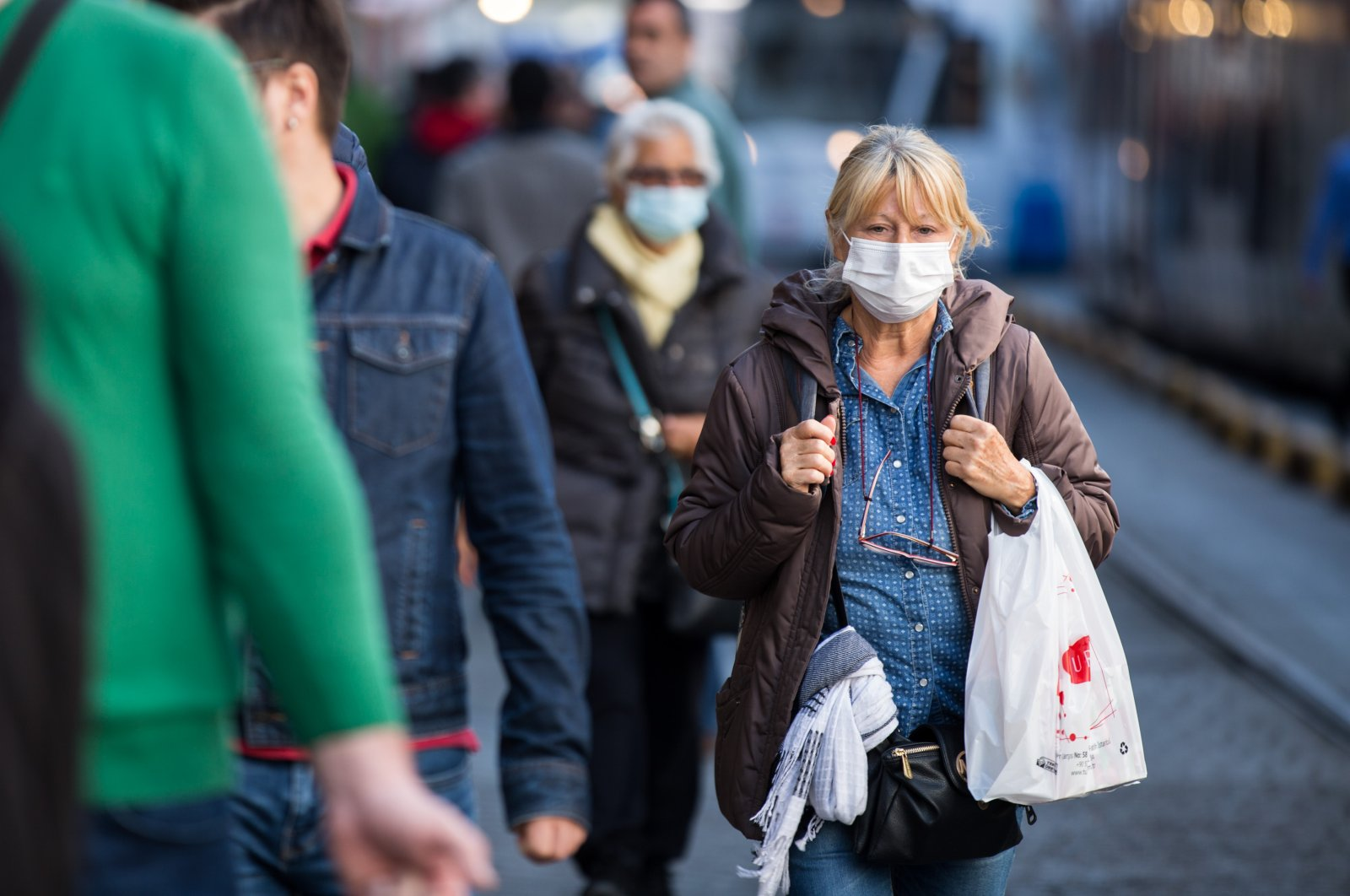 A woman wearing a mask walks on the street, Wednesday, March 11, 2020, in Istanbul. (DHA Photo)