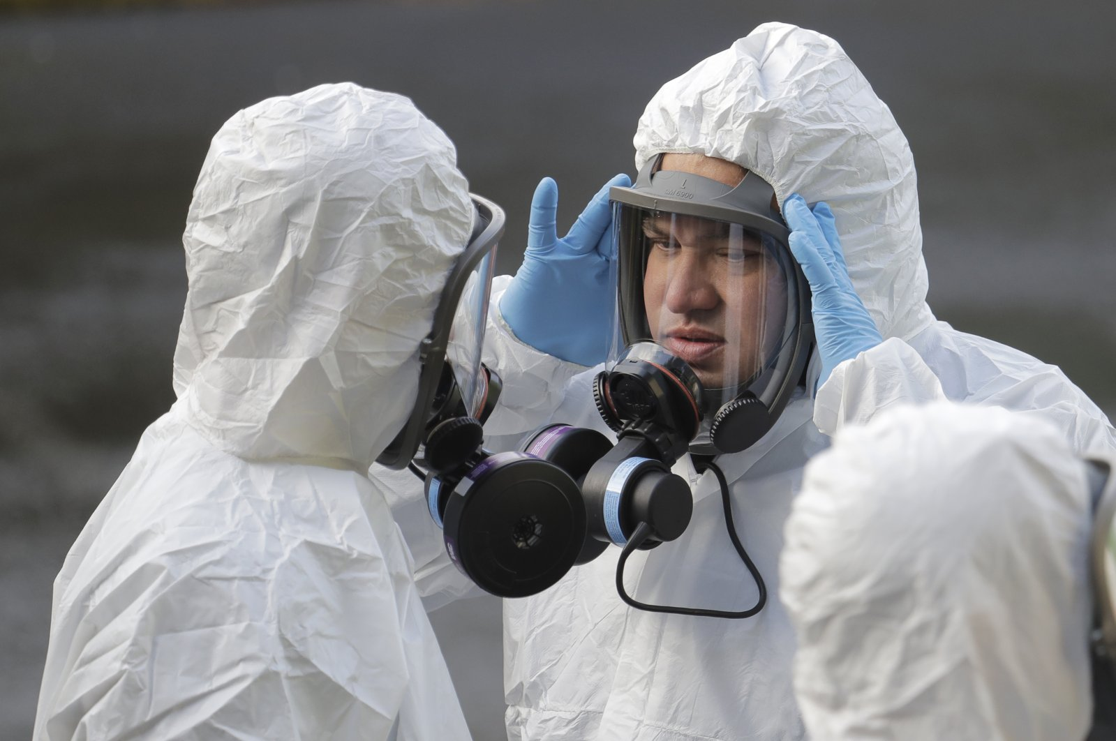 A worker from a Servpro disaster recovery team wearing a protective suit and respirator adjusts his mask before entering the Life Care Center in Kirkland, Wash. to begin cleaning and disinfecting the facility, Wednesday, March 11, 2020, near Seattle. The nursing home is at the center of the outbreak of the COVID-19 coronavirus in Washington state. (AP Photo)