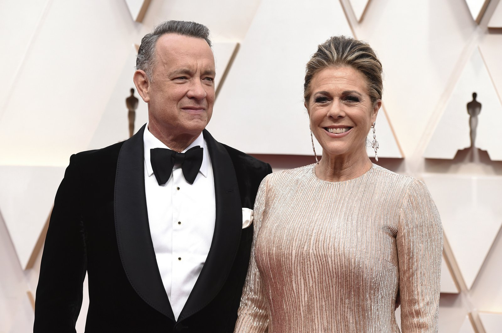 """Tom Hanks, left, and Rita Wilson arrive at the Oscars at the Dolby Theatre in Los Angeles. The couple have tested positive for the coronavirus, the actor said in a statement Wednesday, March 11. The 63-year-old actor said they will be """"tested, observed and isolated for as long as public health and safety requires."""" (AP Photo)"""