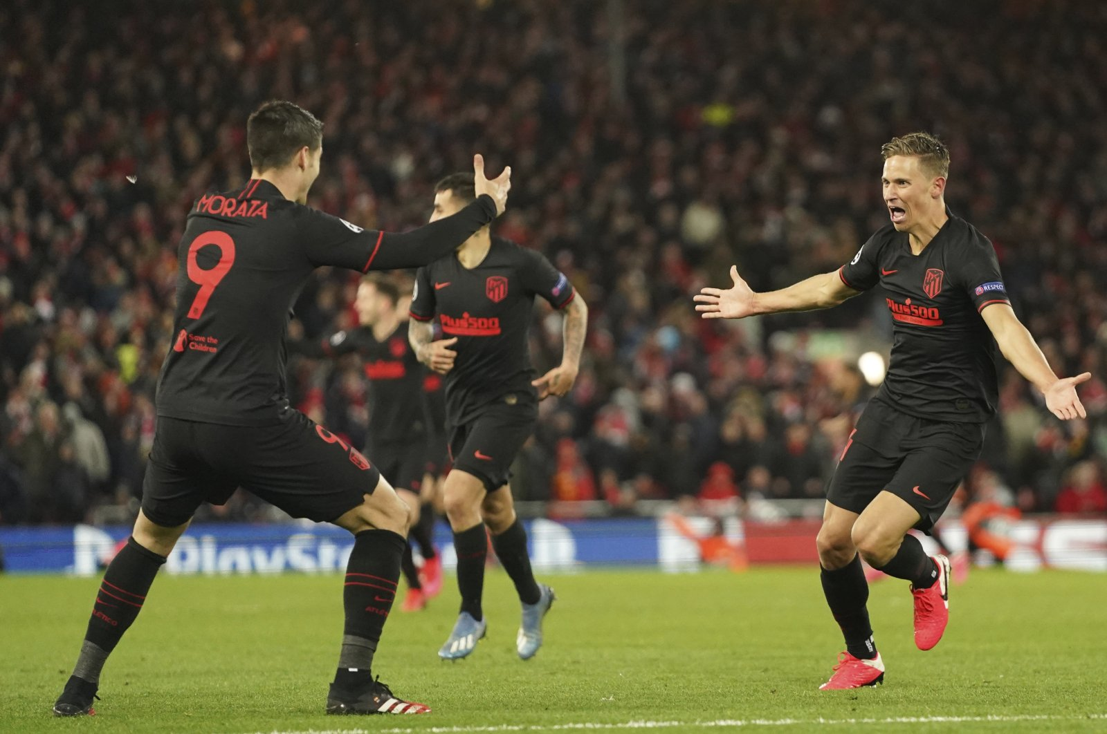 Atletico Madrid's Marcos Llorente, right, celebrates after scoring his side's second goal during a second leg, round of 16, Champions League soccer match between Liverpool and Atletico Madrid at Anfield stadium in Liverpool, England, Wednesday, March 11, 2020. (AP Photo)
