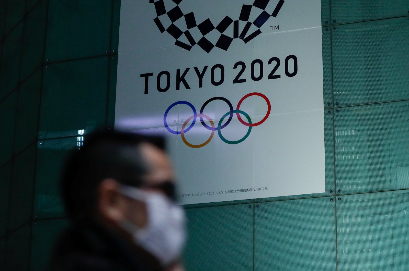 A man wearing a protective face mask walks past a banner for Tokyo 2020 Olympics in Tokyo, March 11, 2020. (Reuters Photo)