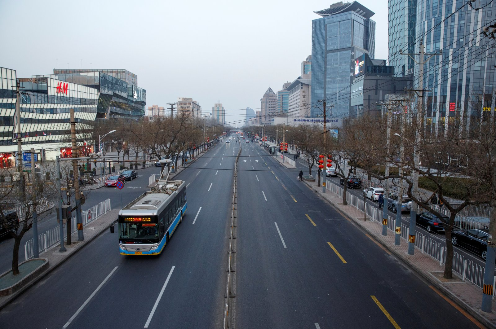 An electric bus goes on a usually busy main road in the Sanlitun shopping district in Beijing, China, Feb. 4, 2019. (Reuters Photo)
