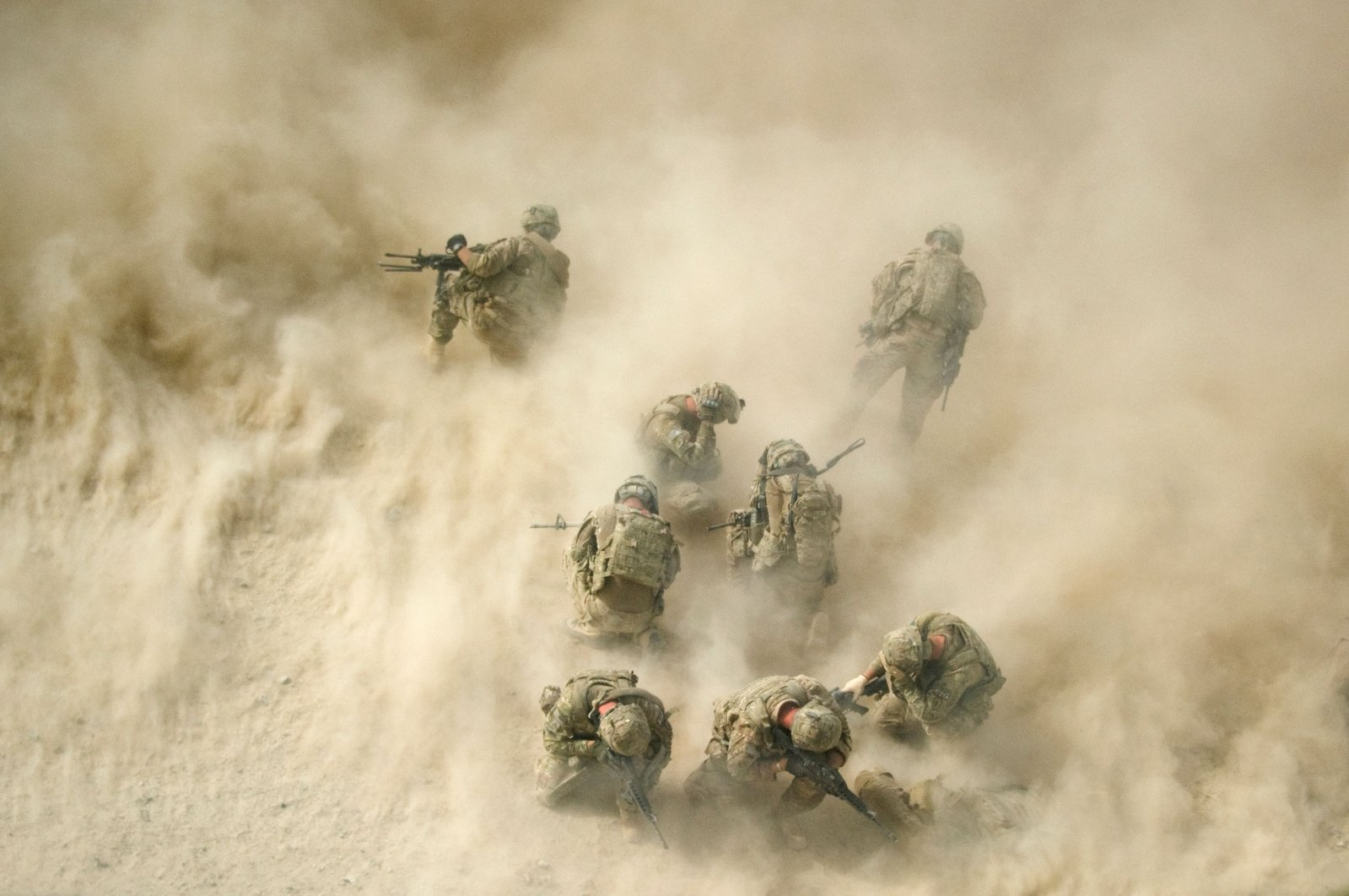 U.S. soldiers gather near a destroyed vehicle and protect their faces from rotor wash, as their wounded comrades are airlifted by a Medevac helicopter from the 159th Brigade Task Force Thunder to Kandahar Hospital Role 3, Aug. 23, 2011. (AFP Photo)