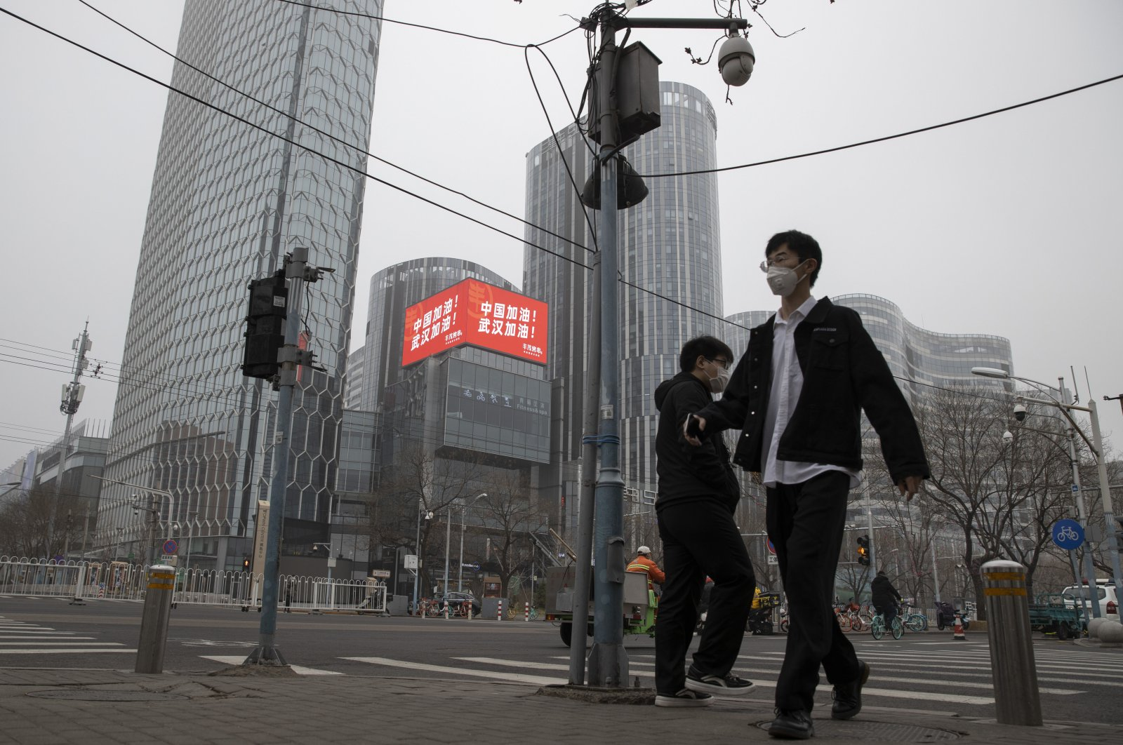 """Residents walk past a retail and office district with a screen showing propaganda which reads """"Go China! Go Wuhan"""" as businesses slowly restart in Beijing on Sunday, March 8, 2020. (AP Photo)"""