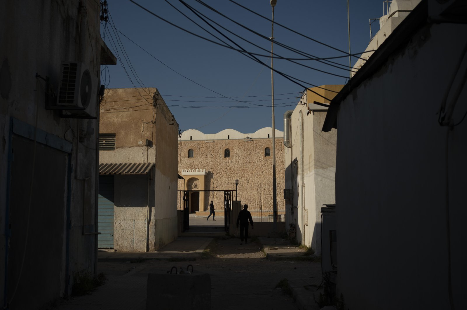 People walk outside a mosque in Tripoli, Libya, on Feb. 27, 2020. Eastern-based Haftar forces attacked Tripoli last spring to wrest it from control of the U.N.-backed government. (AP Photo)