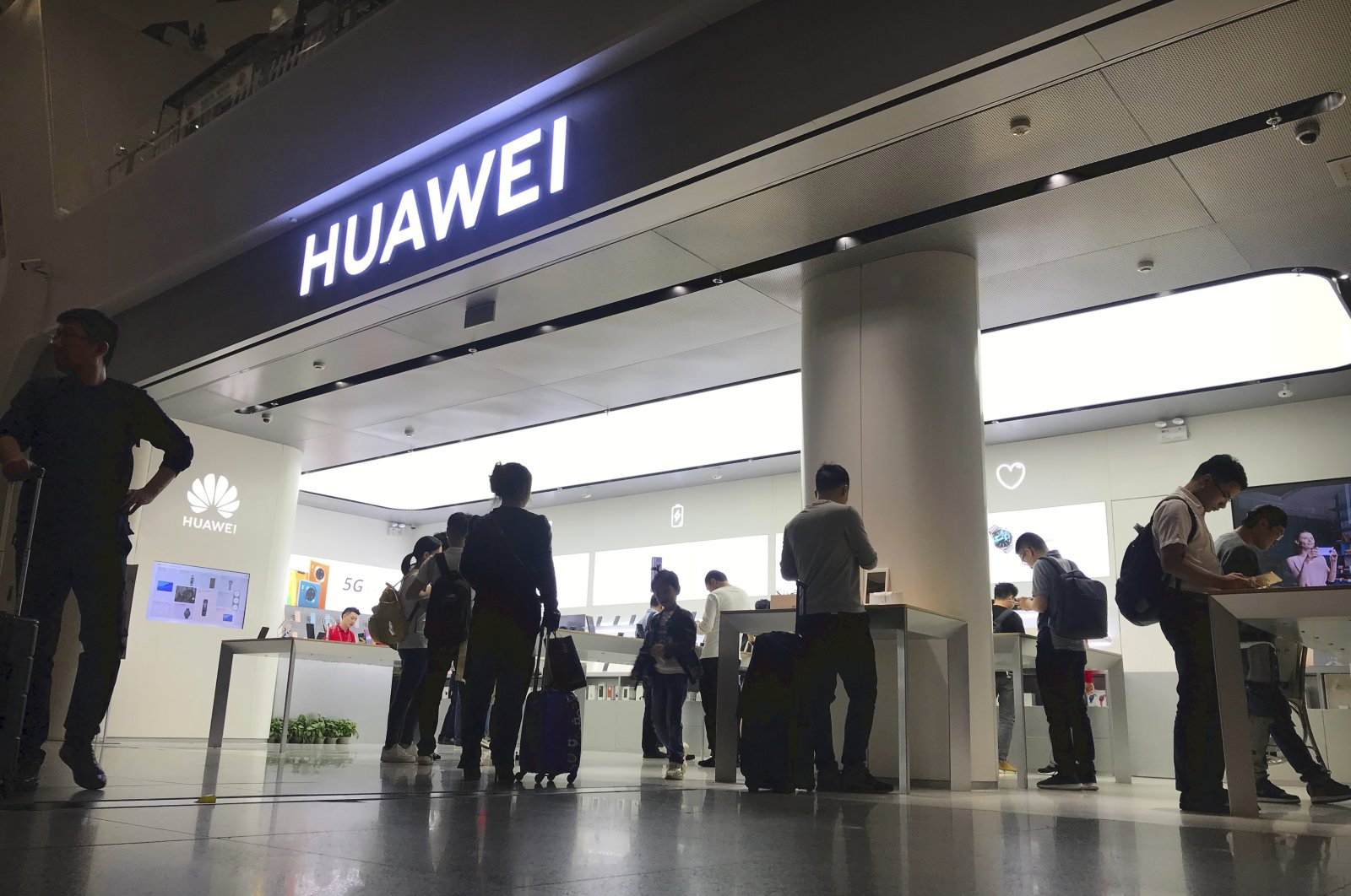 In this Nov. 15, 2019, file photo, people look at a Huawei store in Shenzhen Bao'an International Airport in Shenzhen in southern China's Guangdong Province. (AP File Photo)
