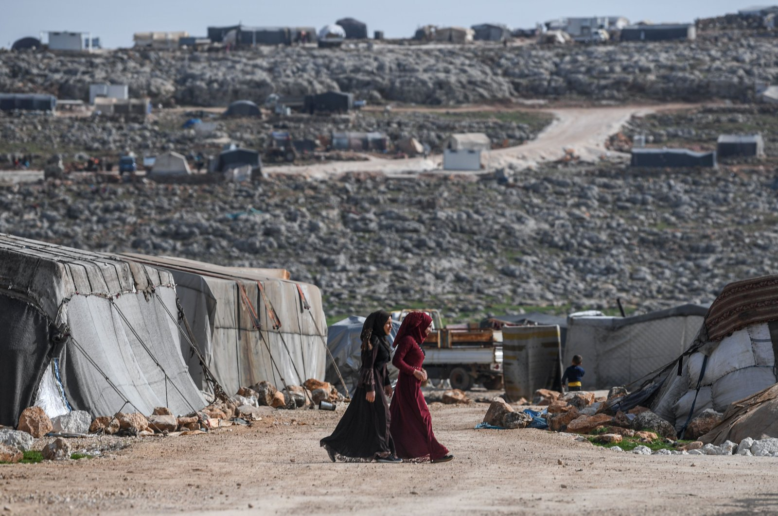 Displaced Syrian women walk at a camp in Kafr Lusin village on the border with Turkey in Syria's northwestern province of Idlib, March 10, 2020. (AFP)