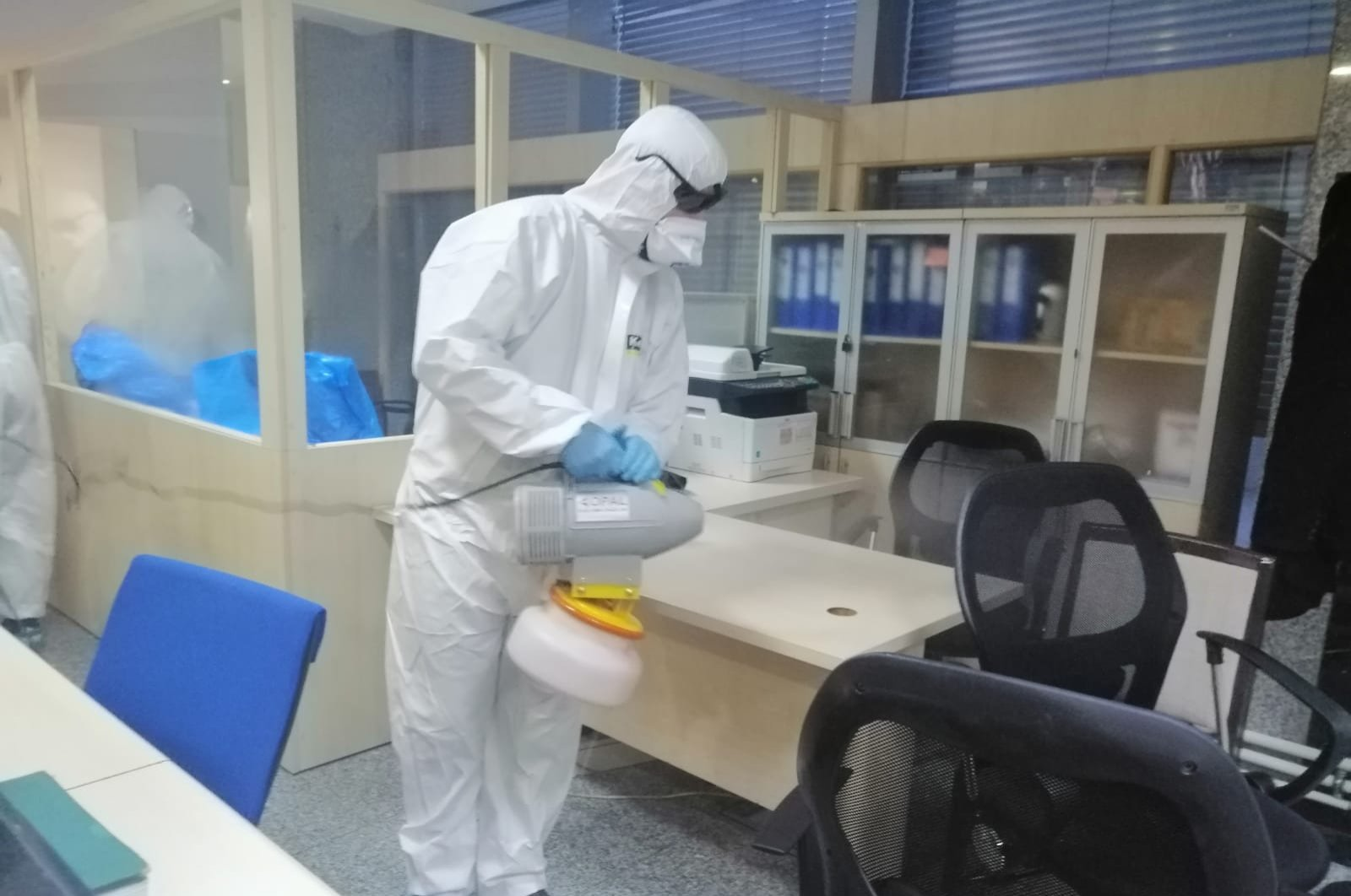 An employee in a protective uniform disinfects an office at the Turkish Parliament, March 11, 2020. (DHA)