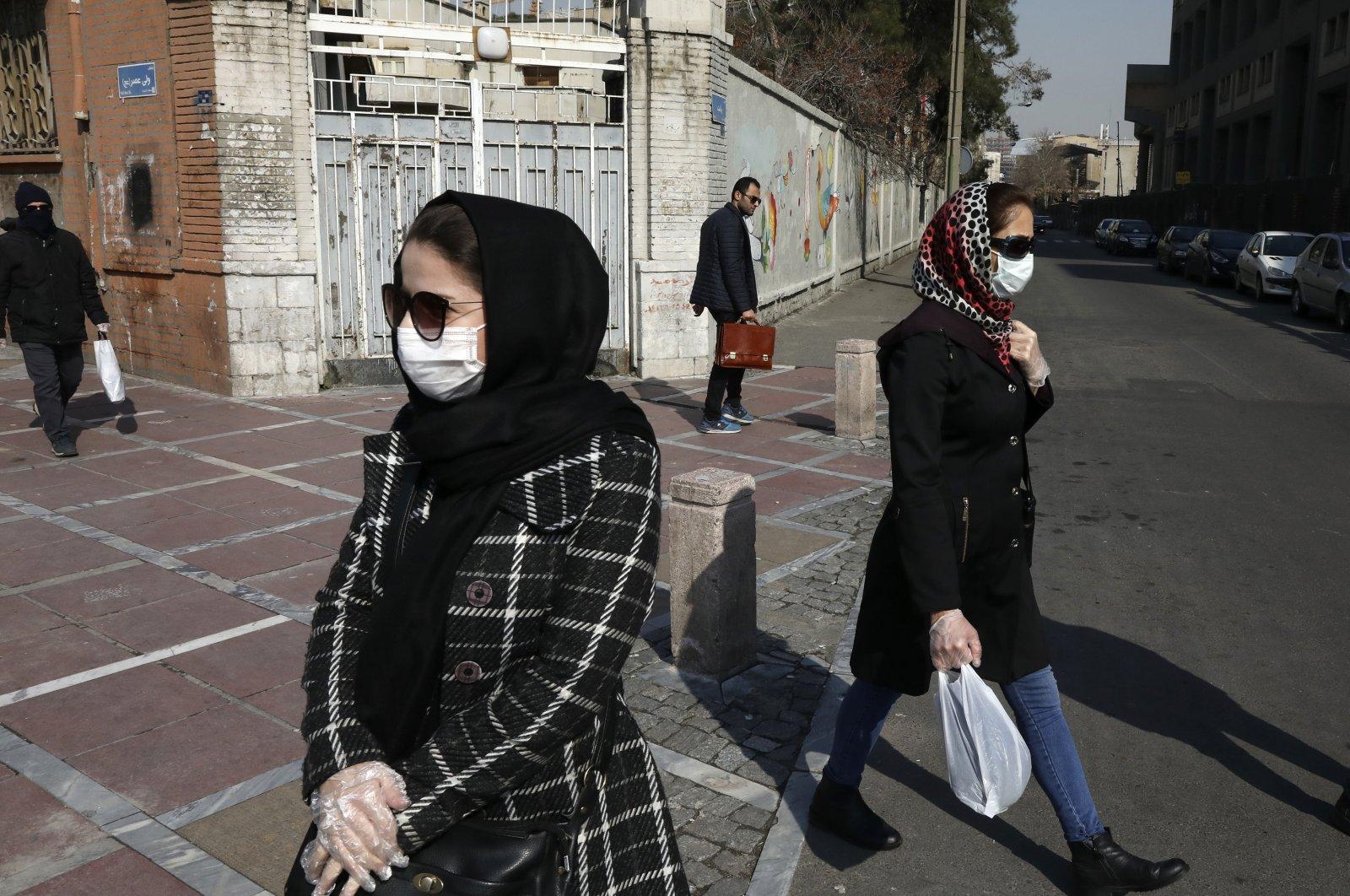 Pedestrians walk as some of them wear masks in downtown Tehran, Iran, Feb. 27, 2020. (AP Photo)