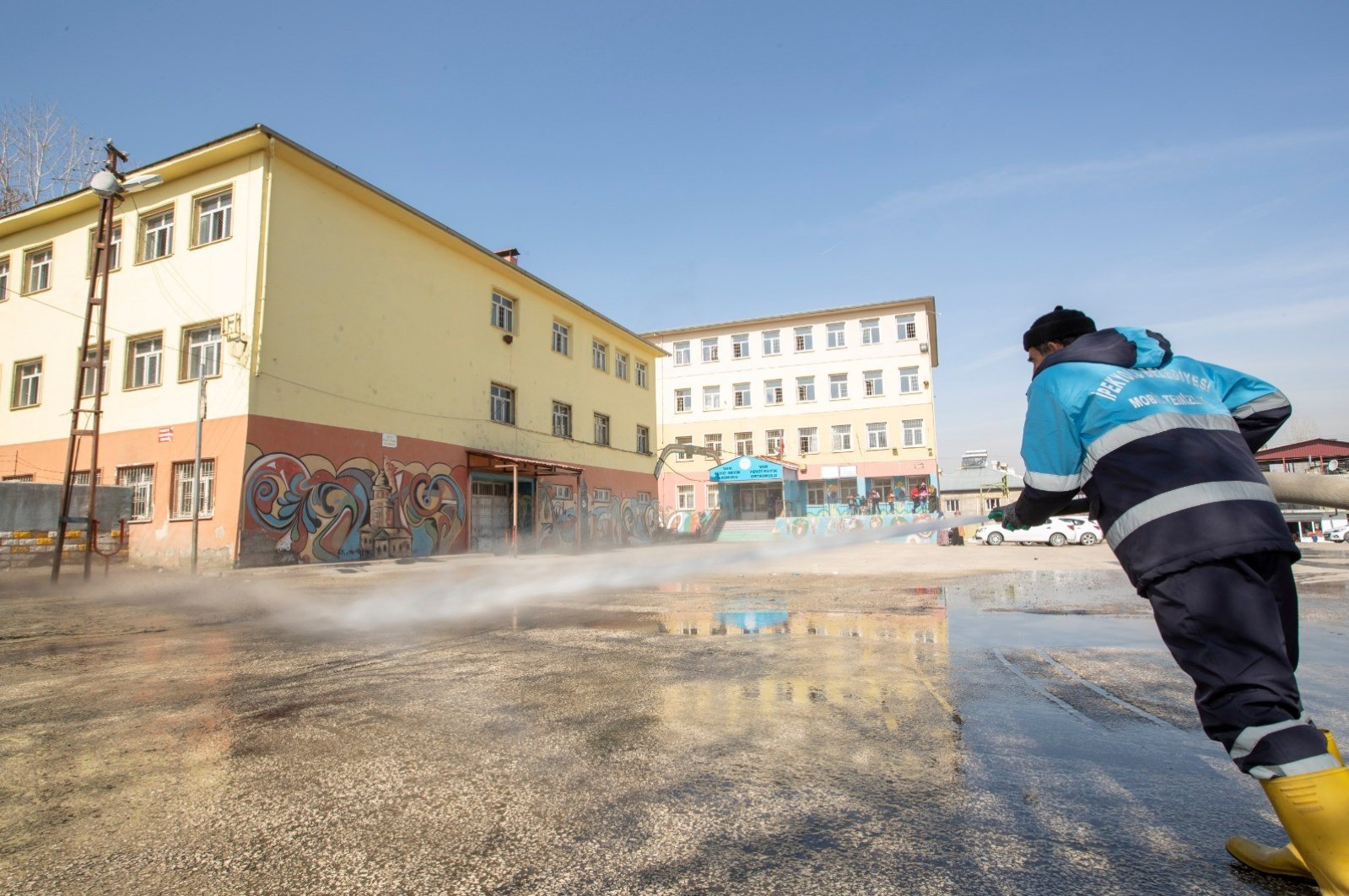 A cleaning worker disinfects school in eastern Van province's Ipekyolu district on Thursday, March 12, 2020 (IHA Photo)