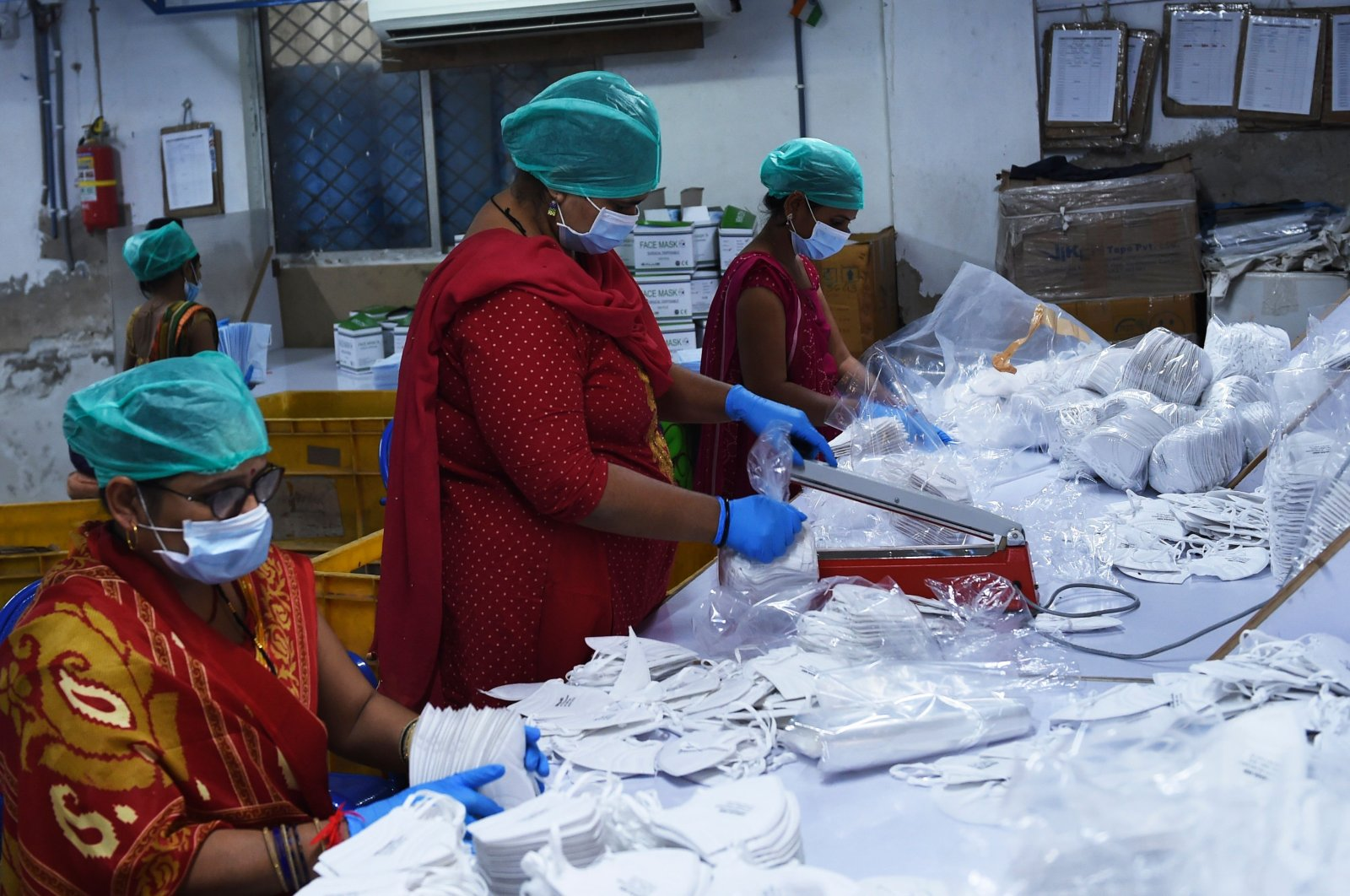 Employees wearing facemasks amid concerns of the spread of the COVID-19 coronavirus work at the production line of facemasks at Salus Products, a manufacturer of surgical disposable products, on the outskirts of Ahmedabad on March 12, 2020. (AFP Photo)