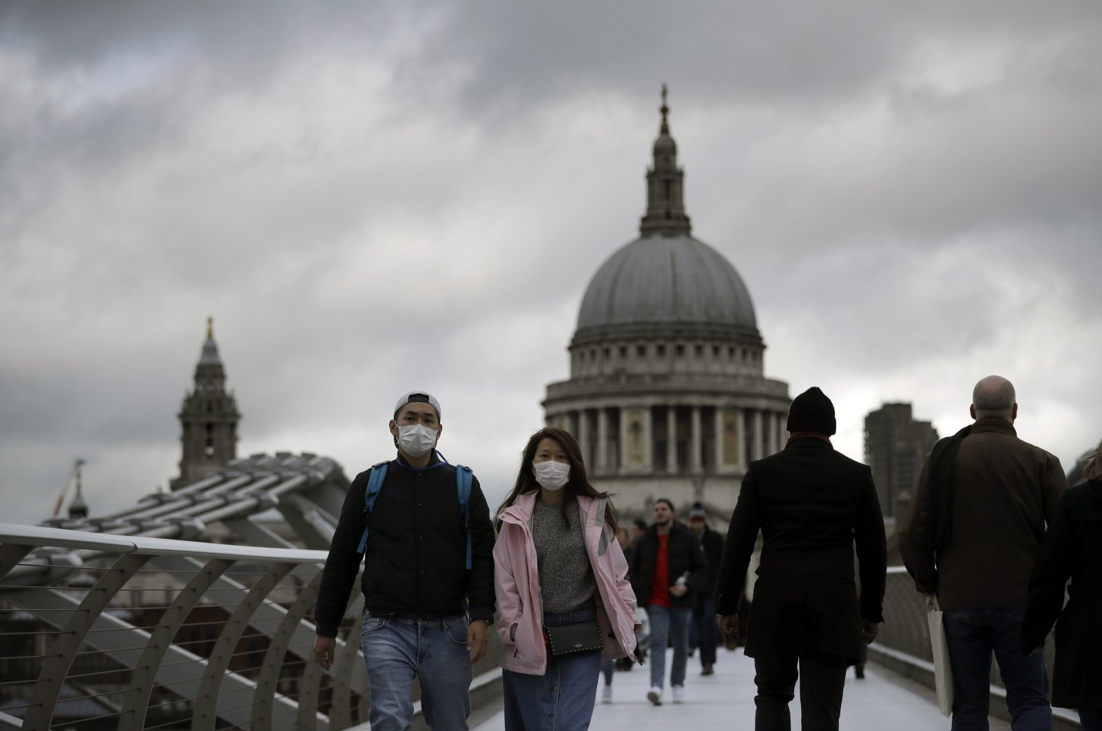 People wearing face masks walk across the Millennium footbridge backdropped by the dome of St. Paul's Cathedral in London, Tuesday, March 10, 2020. (AP Photo)