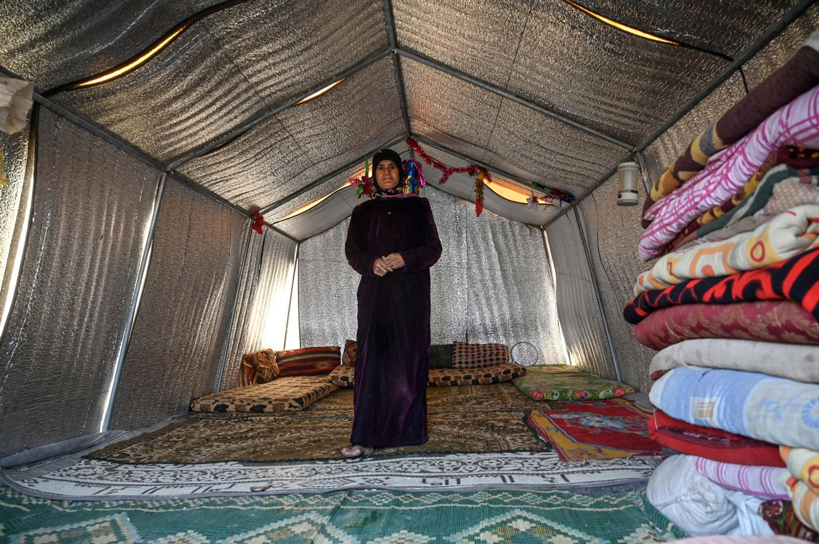Noora al-Ali, ais pictured in her new concrete home at a camp created by Turkey's Humanitarian Relief Foundation (IHH) near Kafr Lusin on the border with Turkey in Syria's northwestern province of Idlib, March 10, 2020. (AFP)