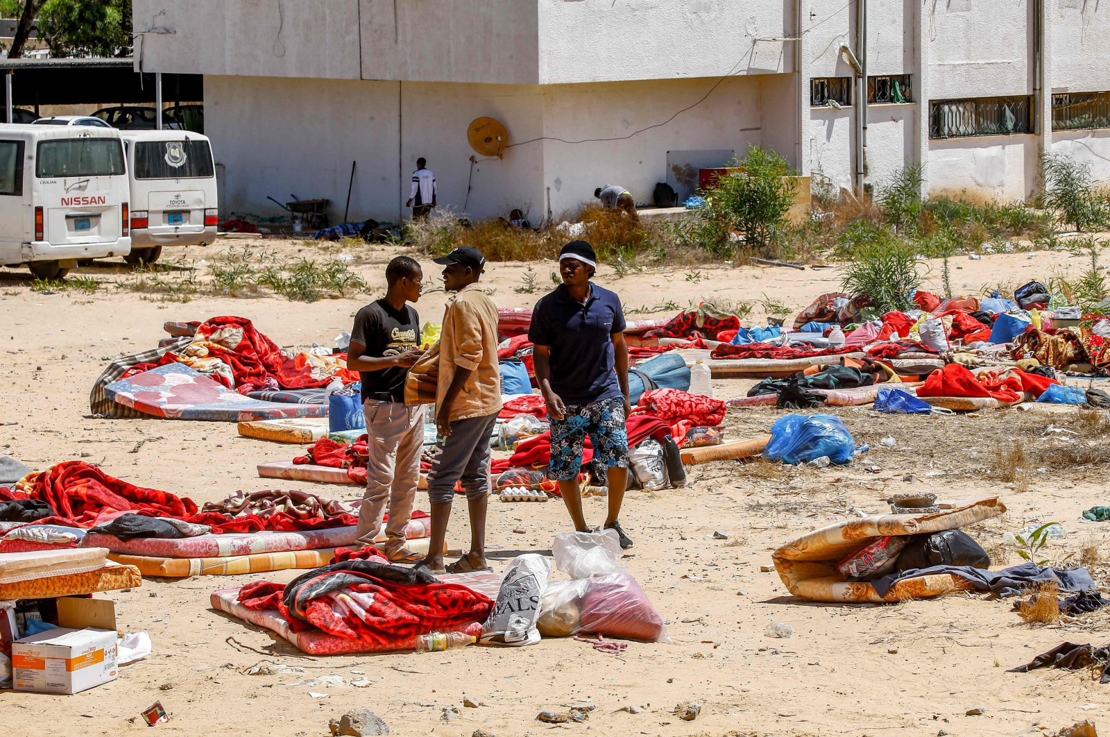 Migrants stand and walk outside at a detention centre used by the Libyan Government of National Accord (GNA) in the capital Tripoli's southern suburb of Tajoura on July 3, 2019, following an airstrike on a nearby building that left dozens killed the previous night. (AFP Photo)