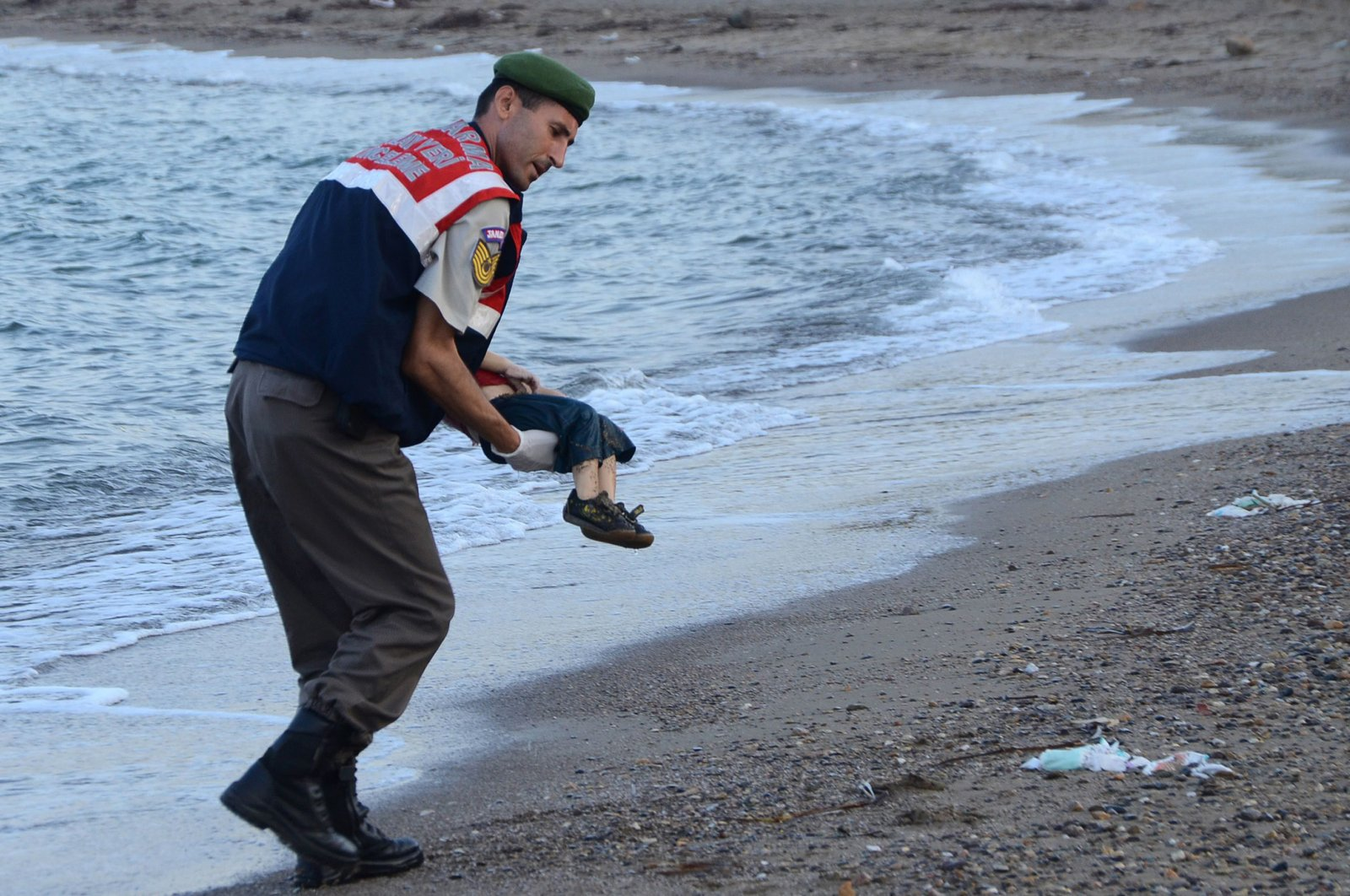 This file photo shows a Turkish gendarmerie officer carrying the dead body of Aylan Kurdi. (AFP Photo)
