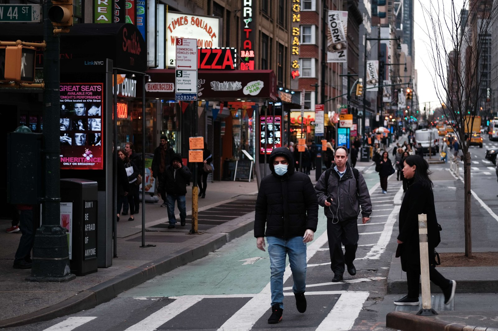 People walk near the Theater District in Manhattan on March 12 in New York City. New York City's Broadway theaters will need to close by 5 p.m. Thursday after New York Gov. Andrew Cuomo announced a ban on gatherings of 500 people or more amid the growing coronavirus outbreak. (AFP Photo)