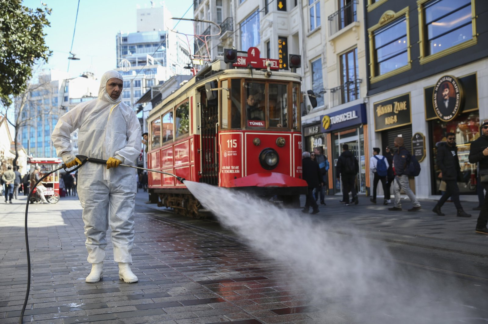 A worker spray disinfectants at famed İstiklal Avenue, Istanbul, March 13, 2020. (AA Photo)