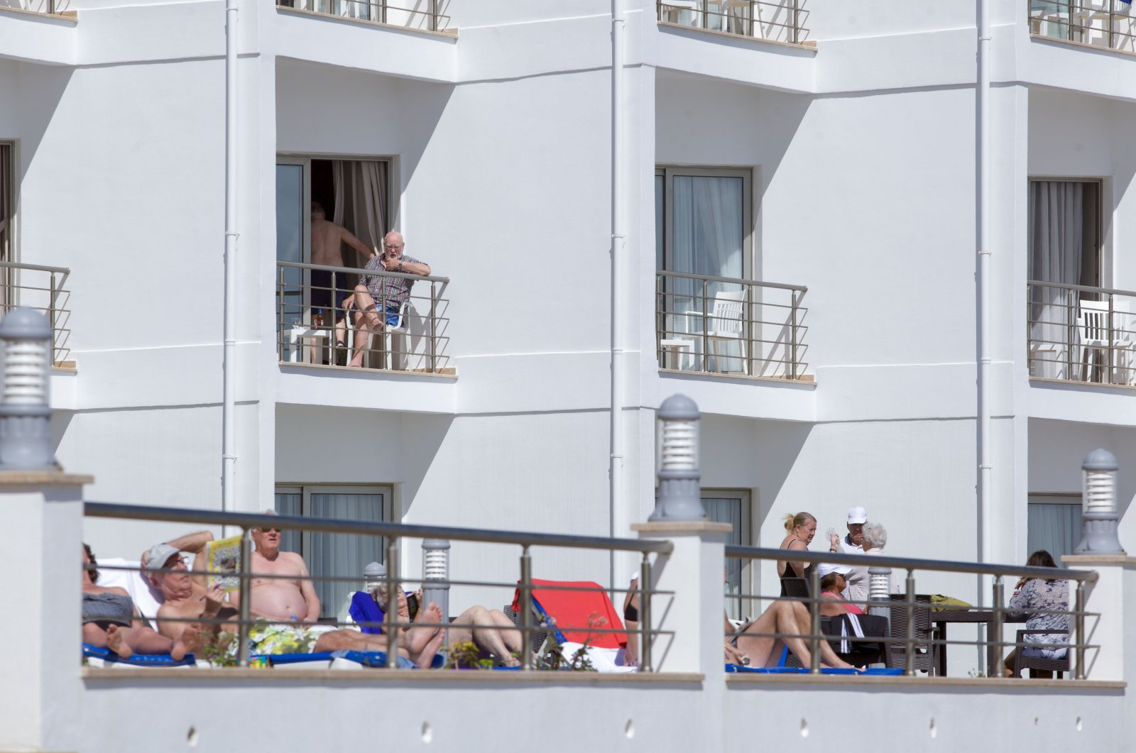 Tourists sit in the sun at the Salamis Bay Conti Hotel, under quarantine due to the novel coronavirus outbreak, in the eastern Cypriot port city of Famagusta in the Turkish Republic of North Cyprus (TRNC), on March 10, 2020. (AFP Photo)