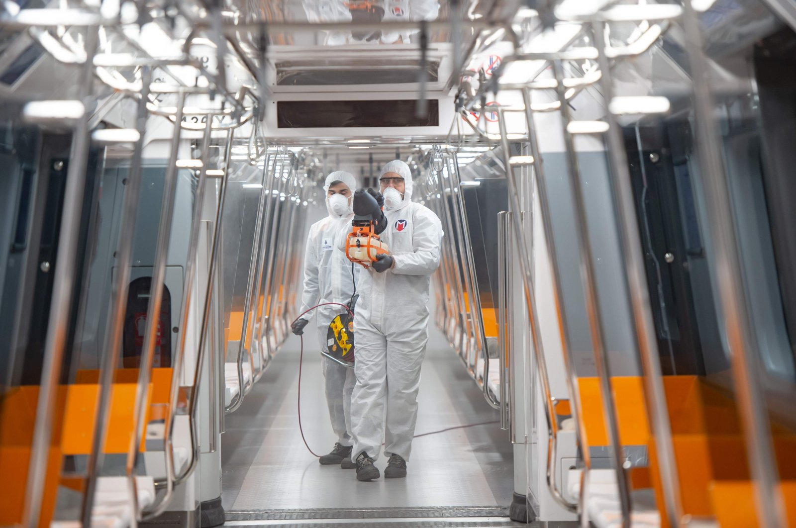 Employees of the Istanbul Municipality wearing protective gear disinfects a subway carriage to prevent the spread of the COVID-19 in Istanbul, March 12, 2020. (AFP Photo)