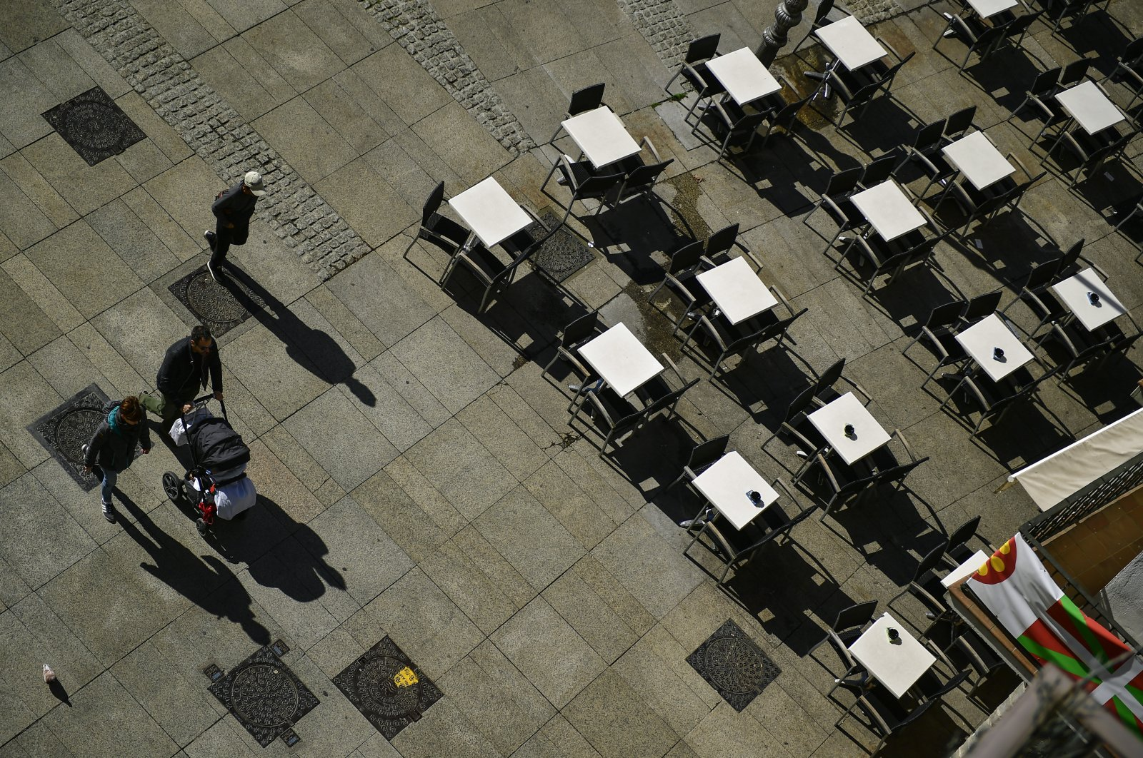Pedestrians pass by an empty bar, in Pamplona, northern Spain, Saturday, March 14, 2020. (AP Photo)