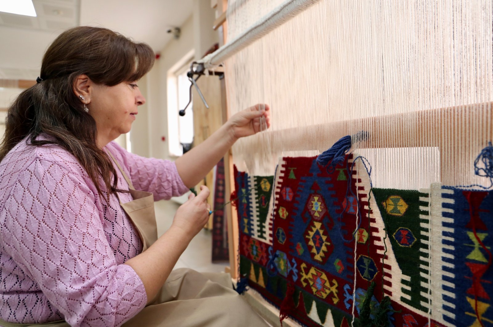 A course attendee weaves her rug at a workshop in Sivrihisar. (AA Photo)
