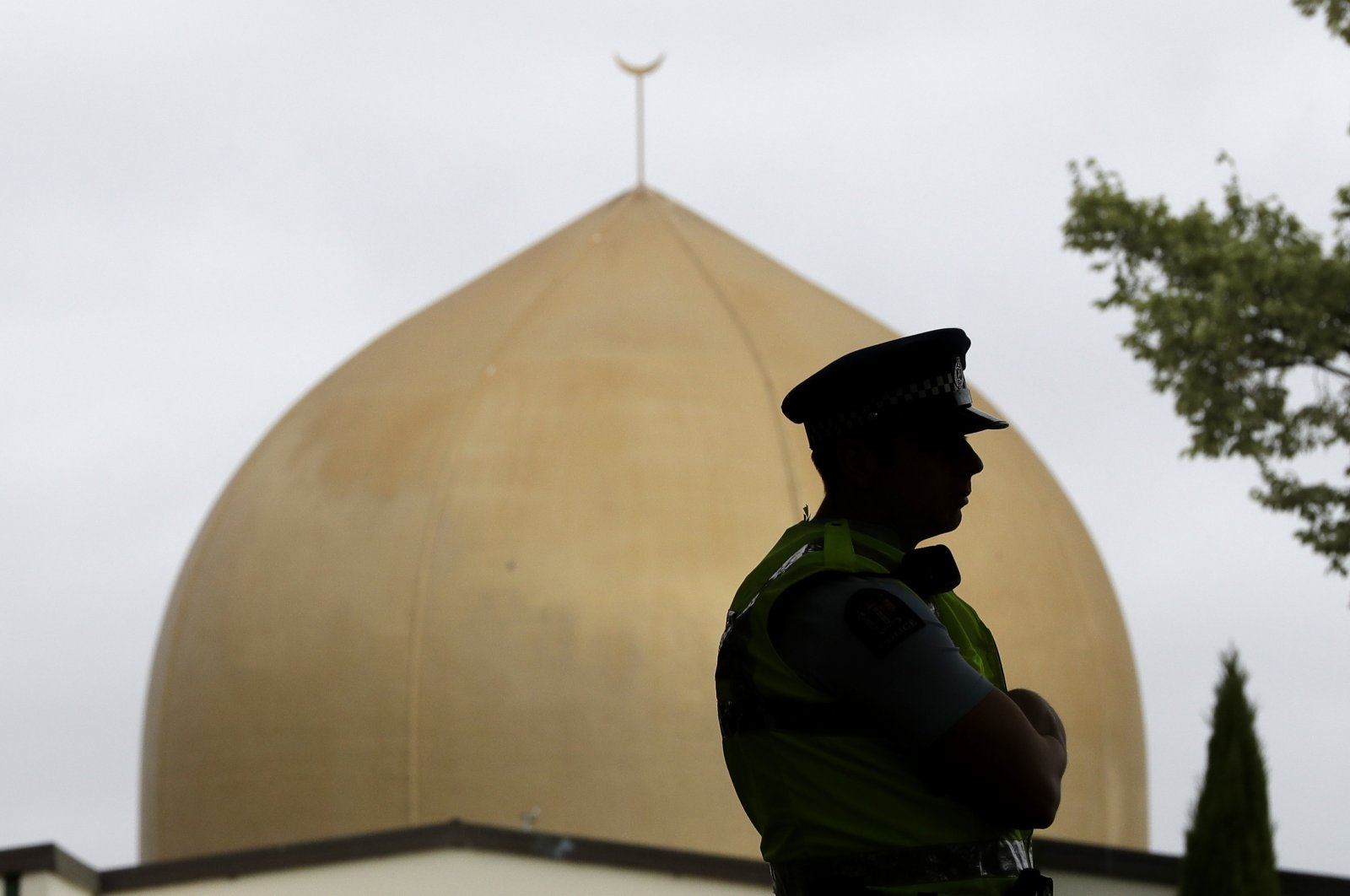 A police officer stands in a park near the Al Noor mosque in Christchurch, New Zealand, Sunday, March 15, 2020. A national memorial in New Zealand to commemorate the 51 people who were killed when a gunman attacked two mosques one year ago has been canceled due to fears over the new coronavirus. (AP Photo)
