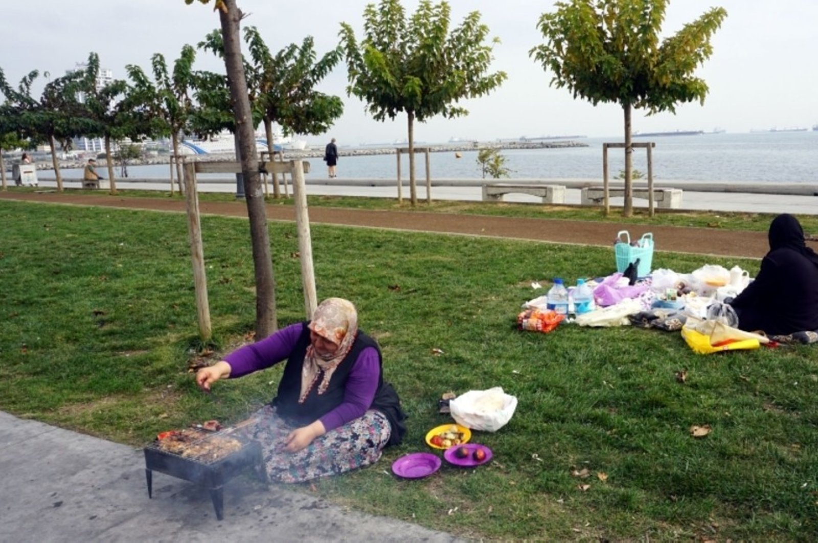 This undated photo shows a woman barbecuing near a seaside promenade in Istanbul. (DHA Photo)