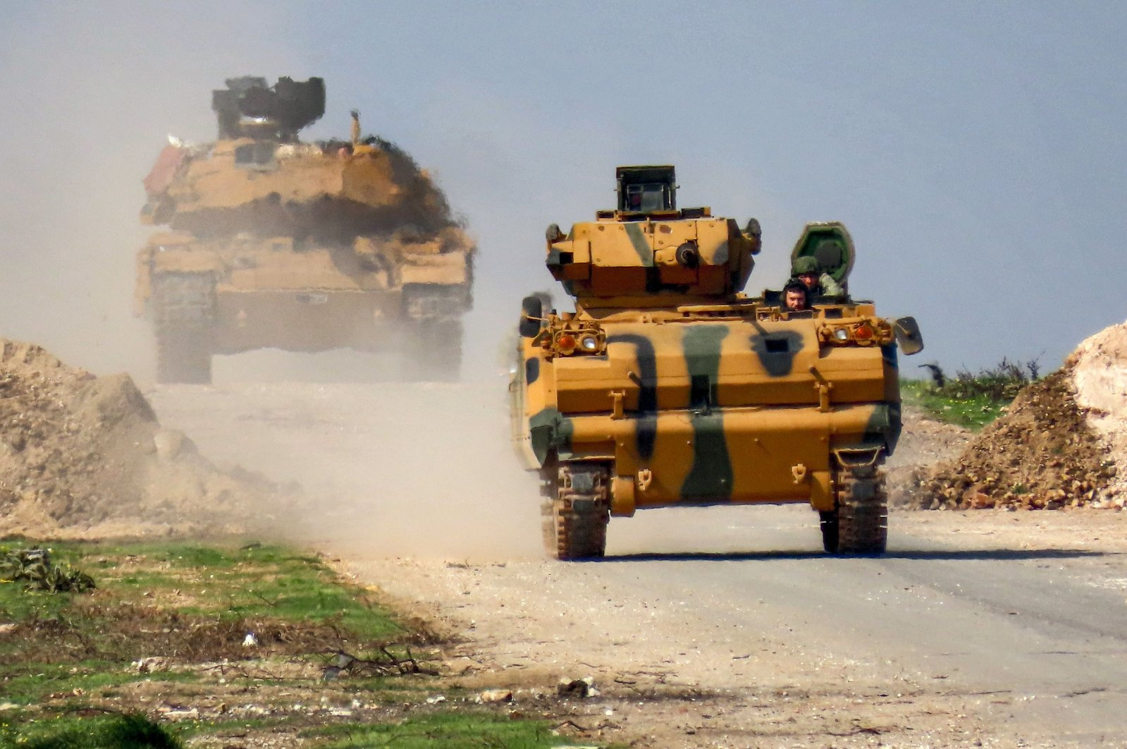 A Turkish military infantry-fighting vehicle (IFV) followed by an M60T battle tank are seen along the M4 highway, which links the northern Syrian provinces of Aleppo and Latakia, before incoming joint Turkish and Russian military patrols (as per an earlier agreed upon cease-fire deal) in the village of al-Nayrab, about 14 kilometers southeast of the city of Idlib and 7 kilometers west of Saraqib in northwestern Syria, March 15, 2020. (AFP)