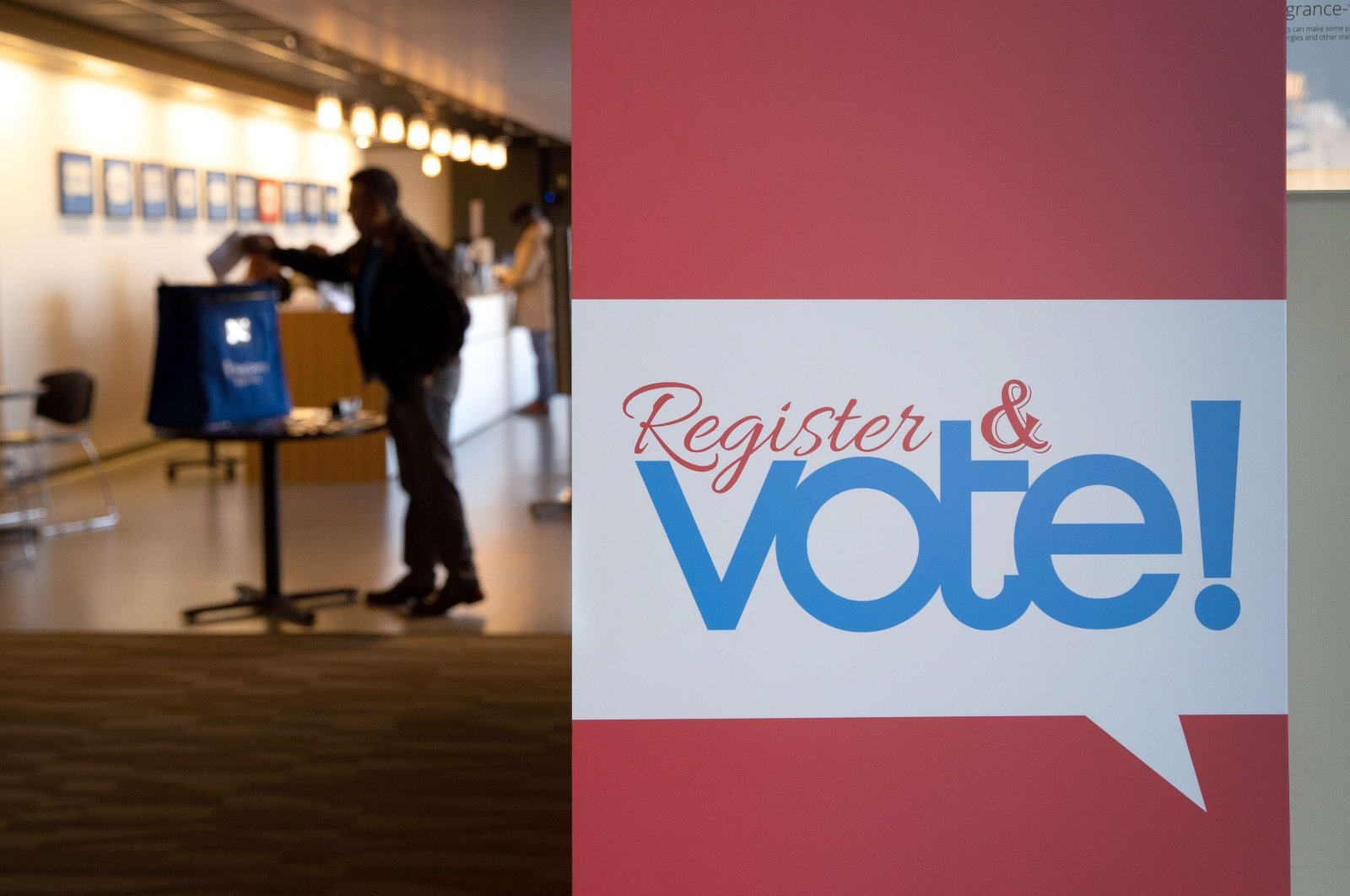 A voter casts his ballot at the King County Elections processing center, in Renton, Washington, Monday, March 9, 2020. (AFP Photo)
