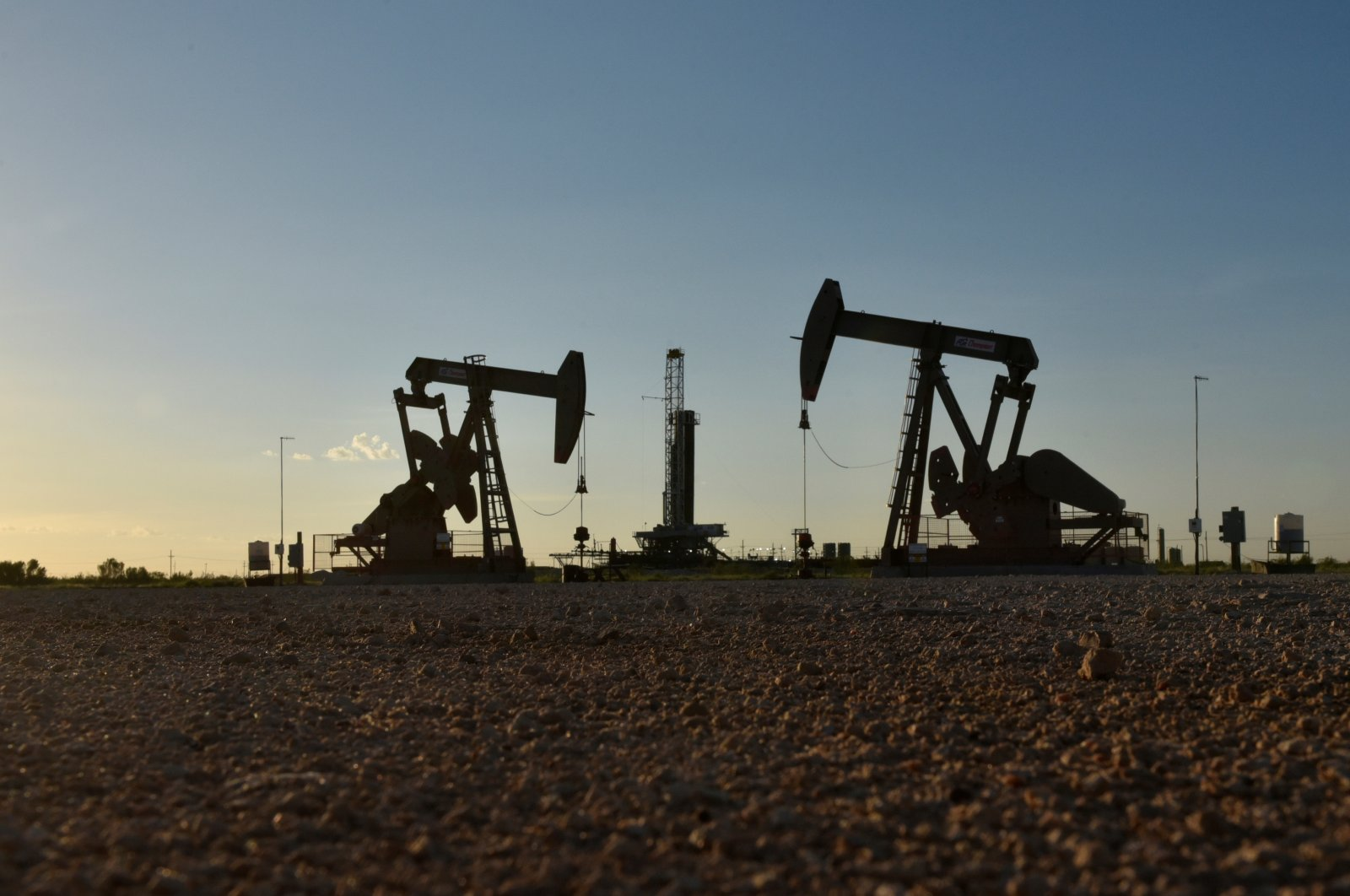 Pump jacks operate in front of a drilling rig in an oil field in Midland, Texas, U.S. Aug. 22, 2018. (Reuters Photo)