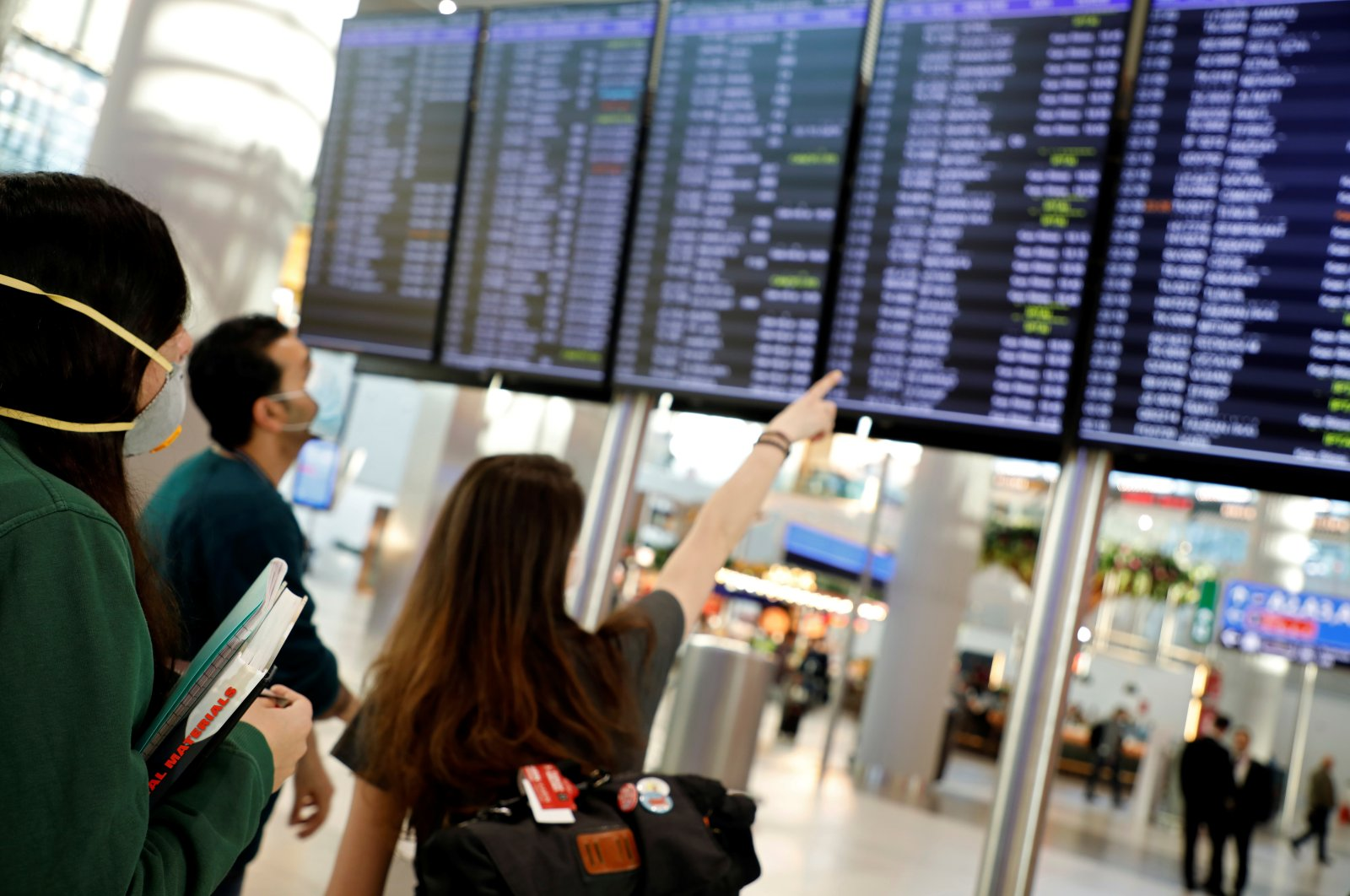 People, wearing protective face masks to protect against the coronavirus, look at flight status information at Istanbul Airport, Friday, March 13, 2020. (Reuters Photo)