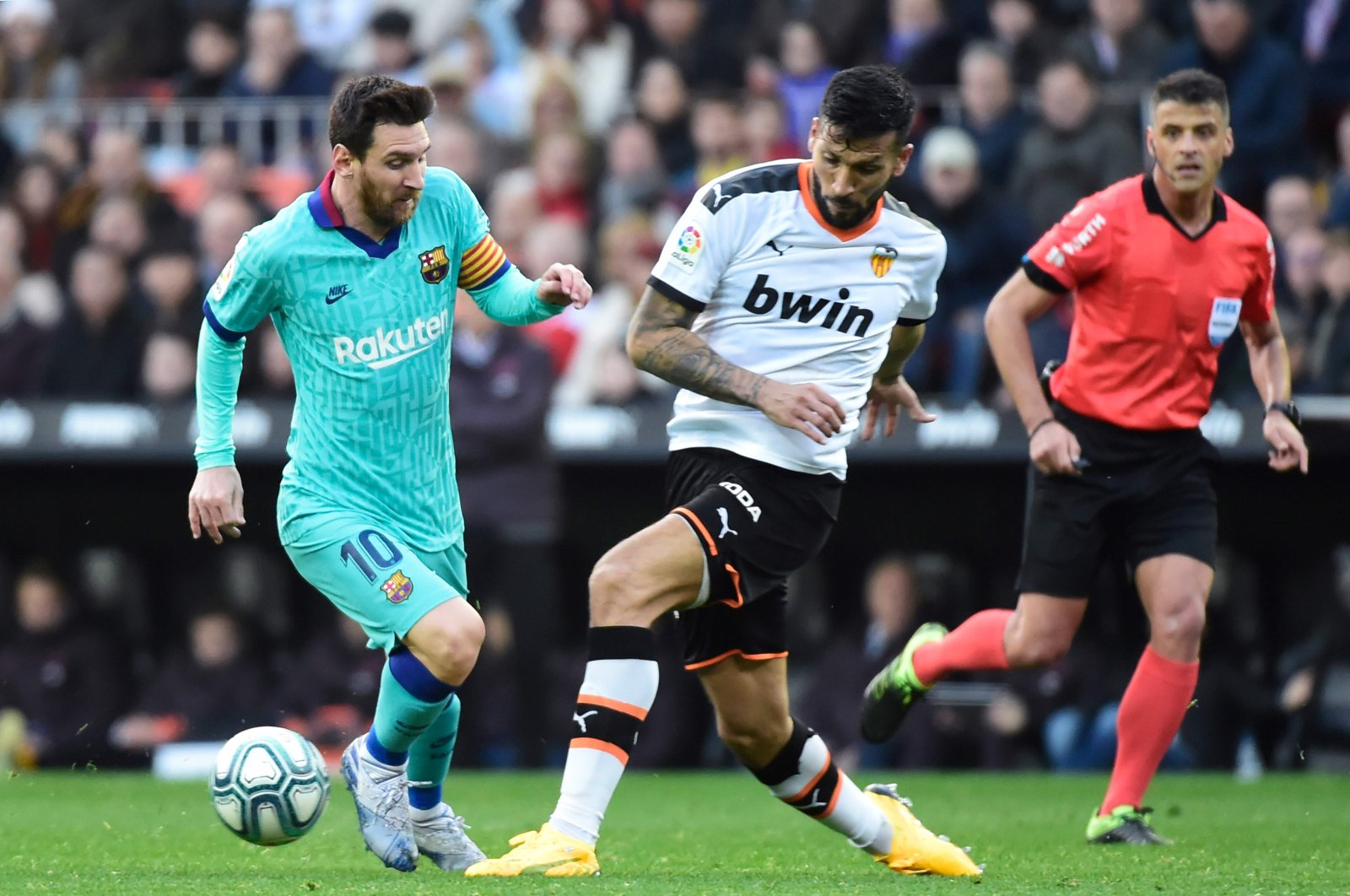 Ezequiel Garay (C) challenges Barcelona's Lionel Messi(L), Valencia, Jan. 25, 2020. (AFP Photo)
