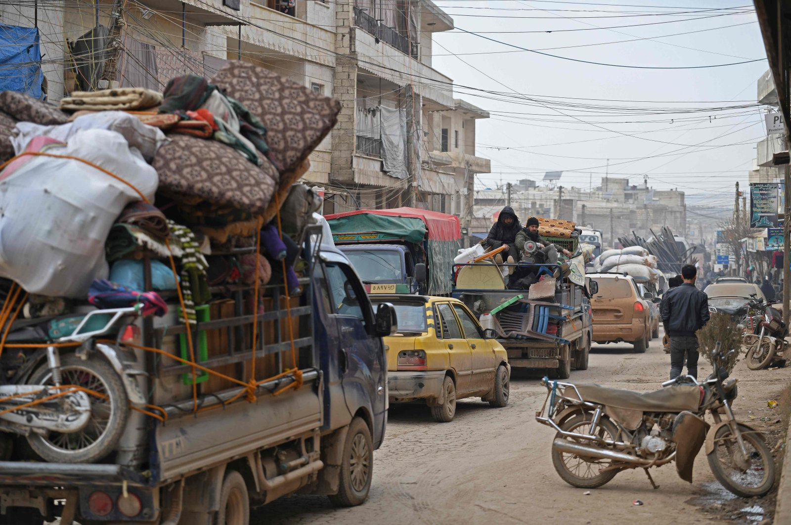 Vehicles carrying internally-displaced persons (IDPs) and their belongings drive through the Syrian town of Atme near the Turkish border towards the city of Afrin, as people flee advancing Syrian regime forces in Idlib and Aleppo provinces, Feb. 17, 2020. (AFP)