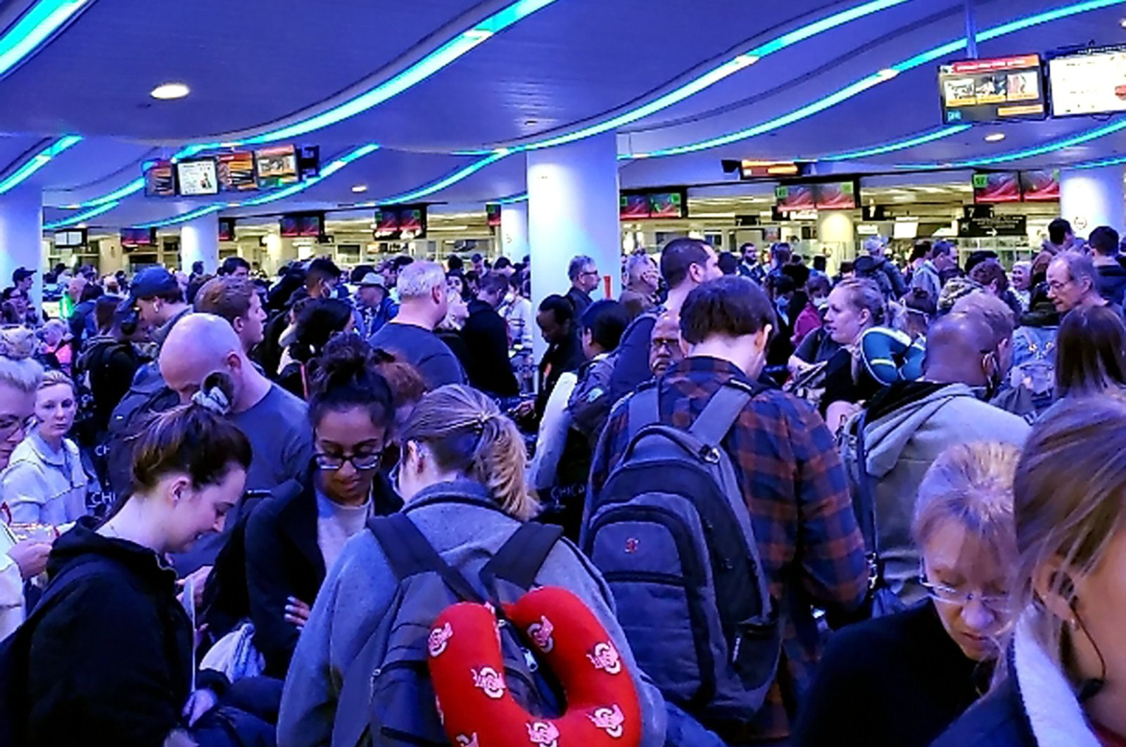 In this Saturday, March 14, 2020 photo provided by Elizabeth Pulvermacher, travelers returning from Madrid wait in a coronavirus screening line at Chicago's O'Hare International Airport. (Elizabeth Pulvermacher via AP)